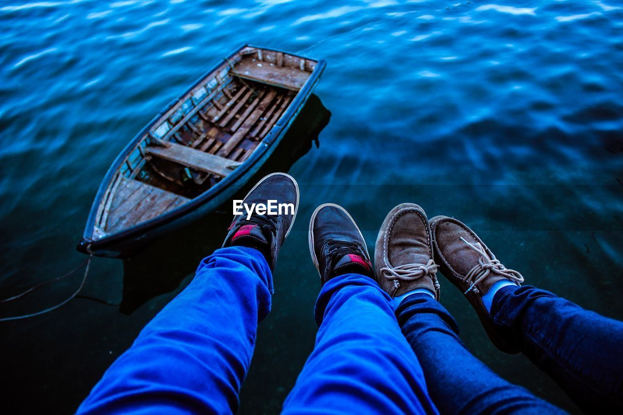 Low section of friends sitting by boat moored at lake
