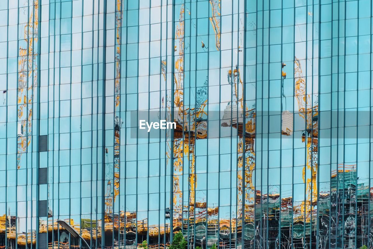 Reflection Of Cranes In Modern Glass Building