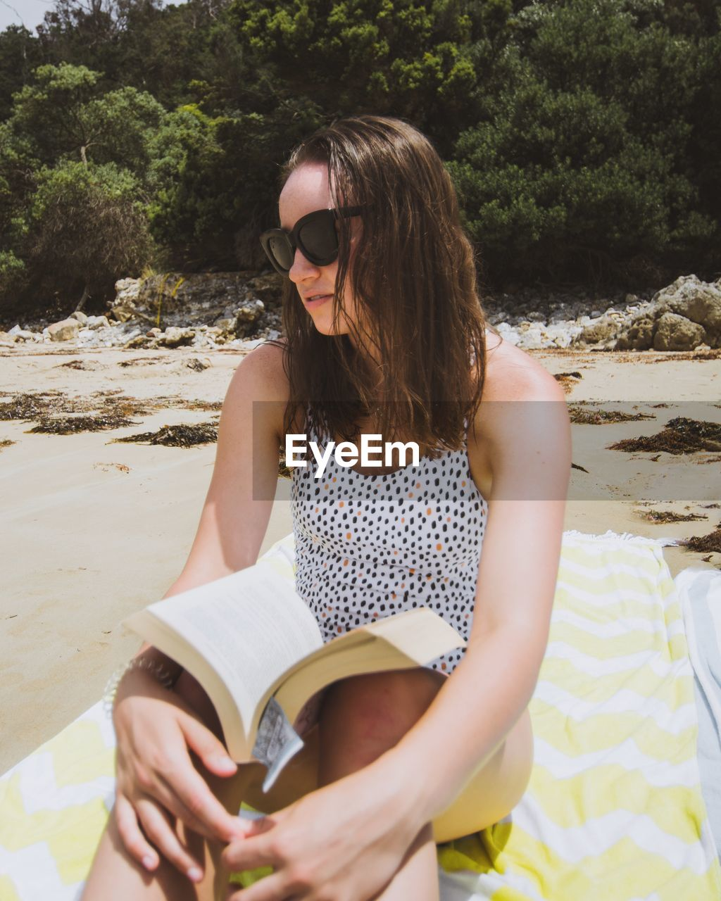 YOUNG WOMAN READING BOOK WHILE SITTING AT BEACH