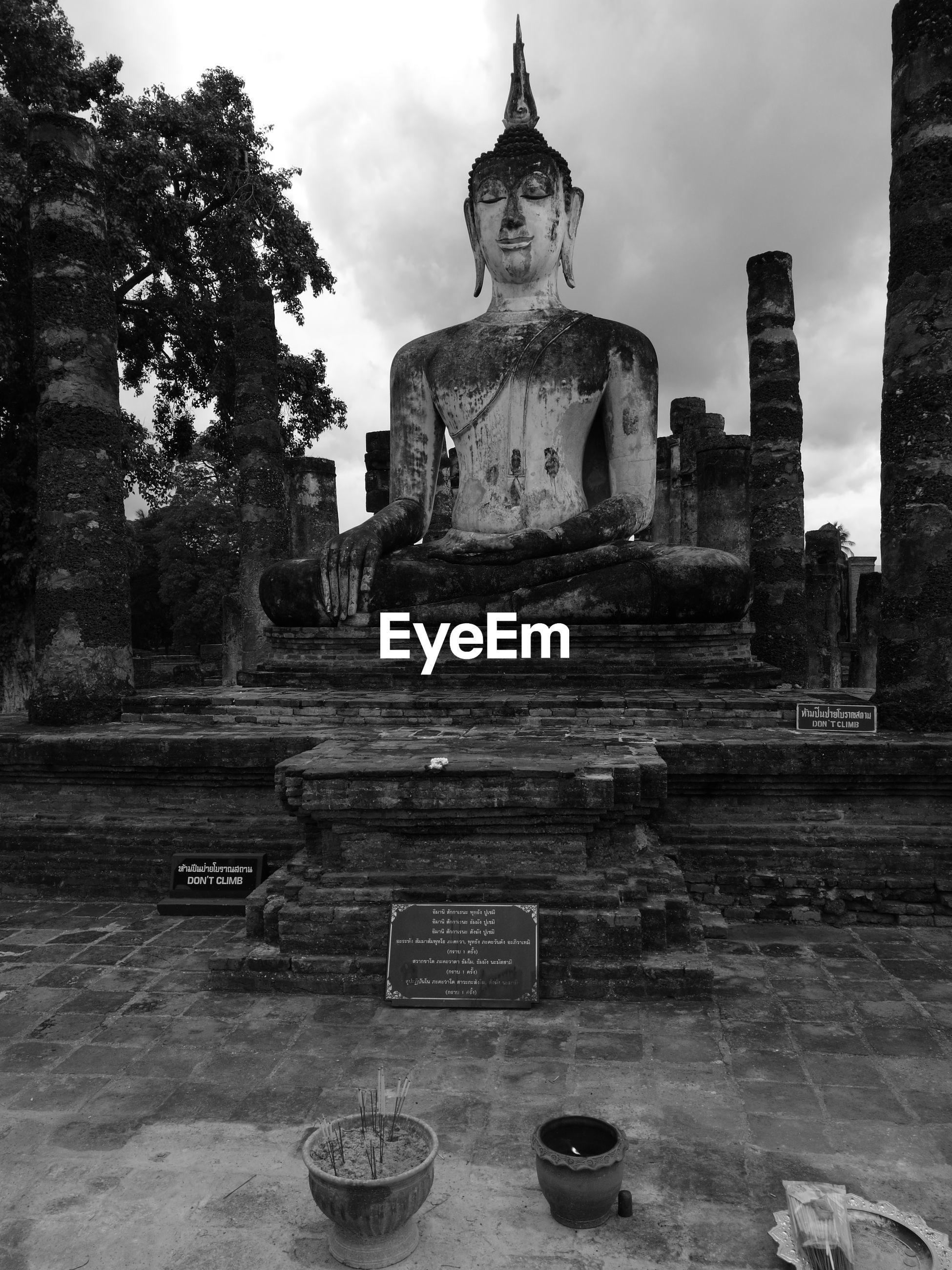 Buddha statue against sky at sukhothai historical park