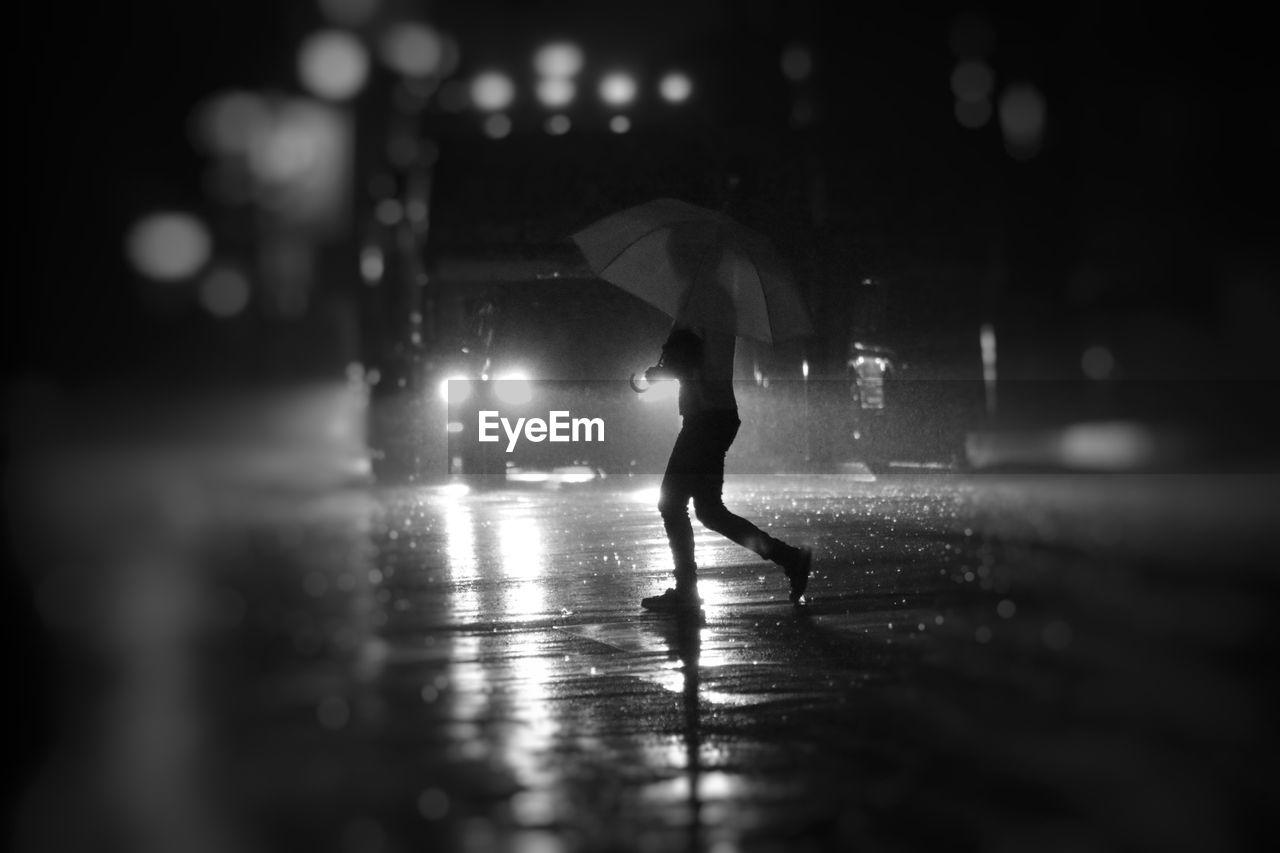 Side view of silhouette woman in umbrella walking on road in rainy season