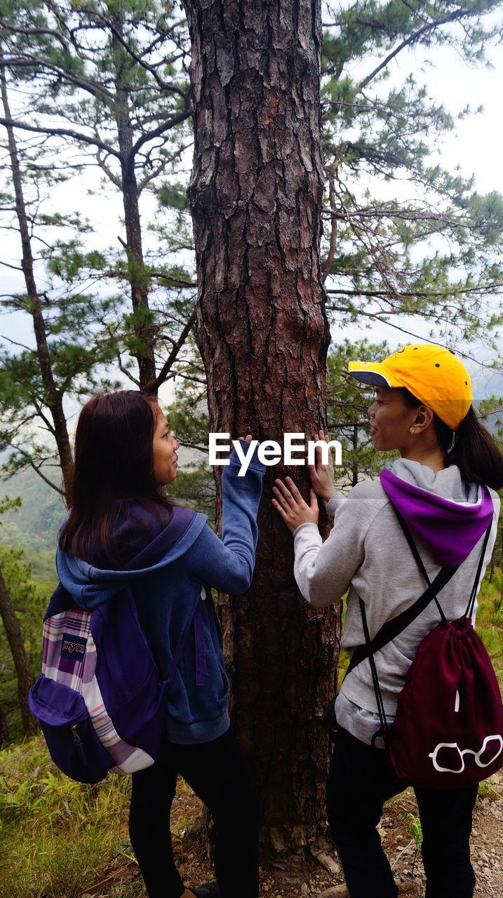 WOMEN STANDING ON TREE TRUNK