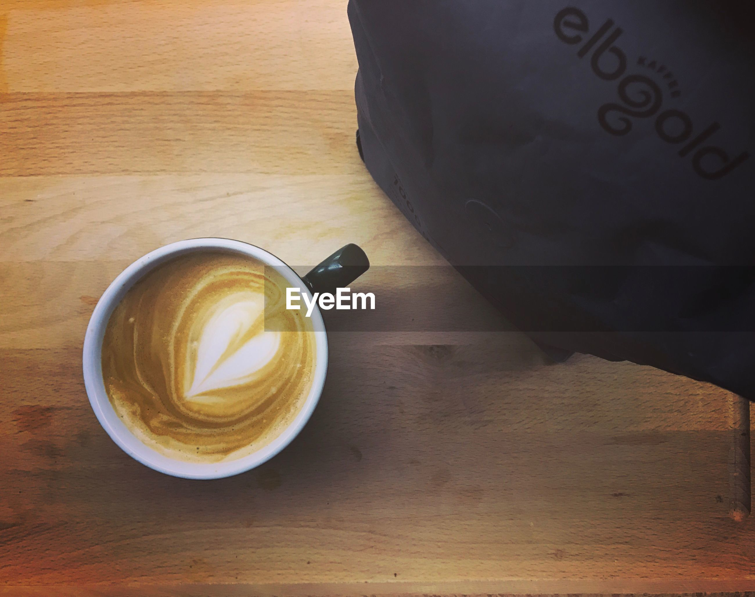 High angle view of cappuccino in cup by paper bag on wooden table