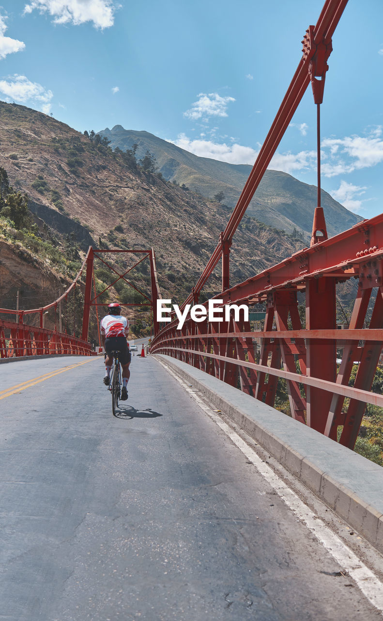MAN RIDING BICYCLE ON BRIDGE AGAINST SKY