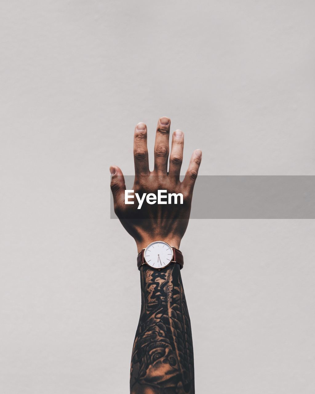 Cropped Image Of Man Hand With Tattoo Wearing Wrist Watch Against White Background