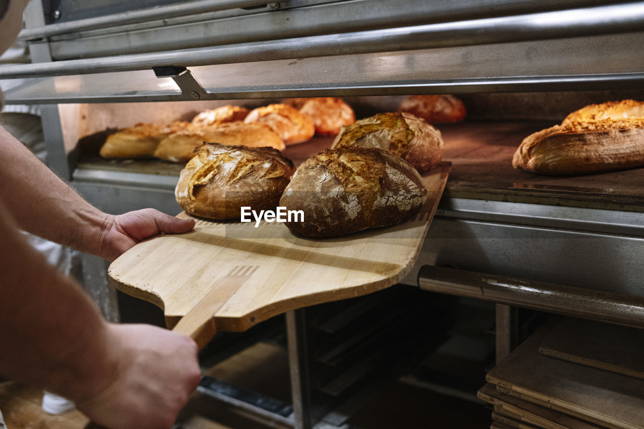 CLOSE-UP OF PERSON PREPARING FOOD IN TRAY