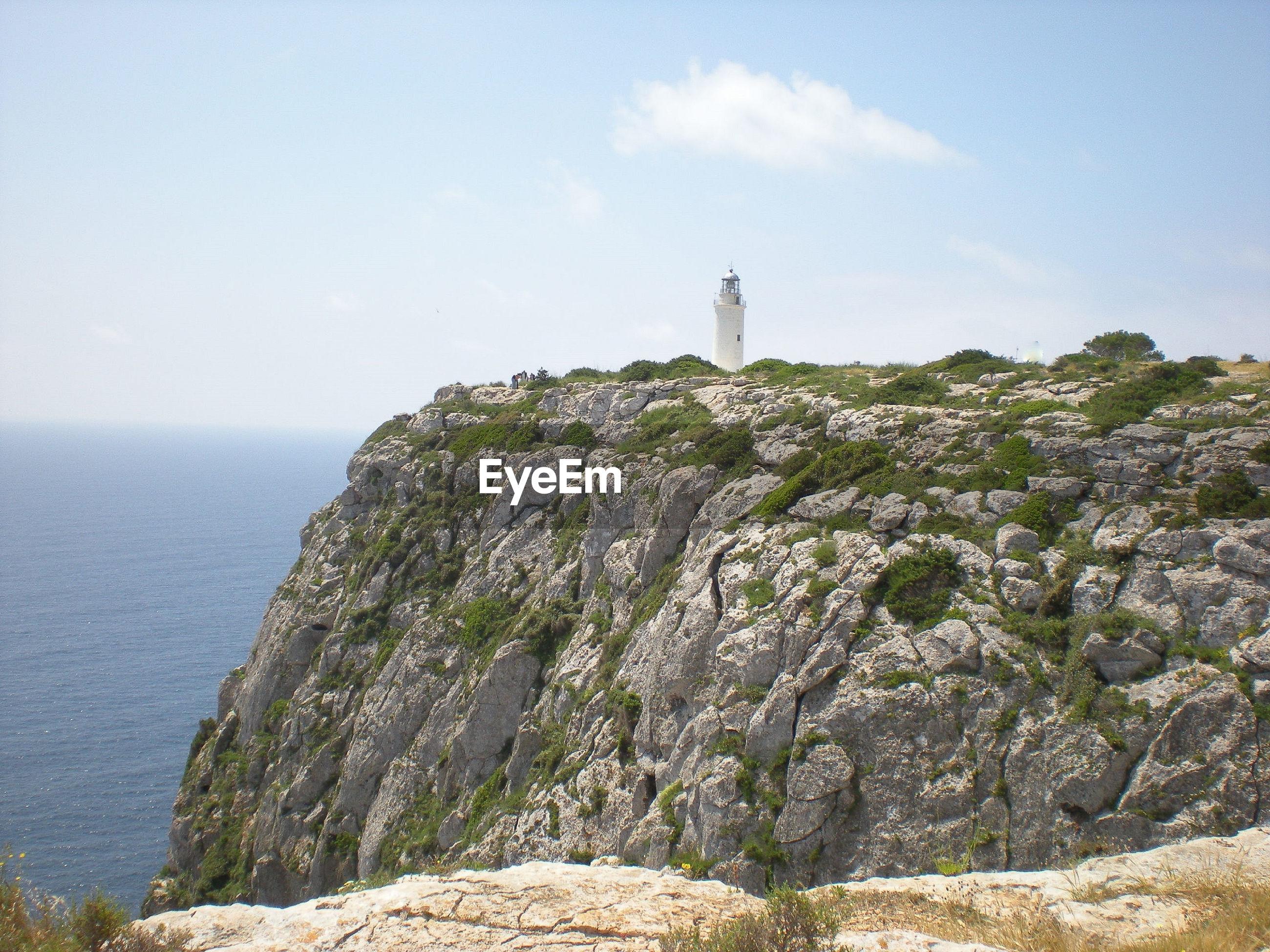 Lighthouse amidst rocks and sea against sky