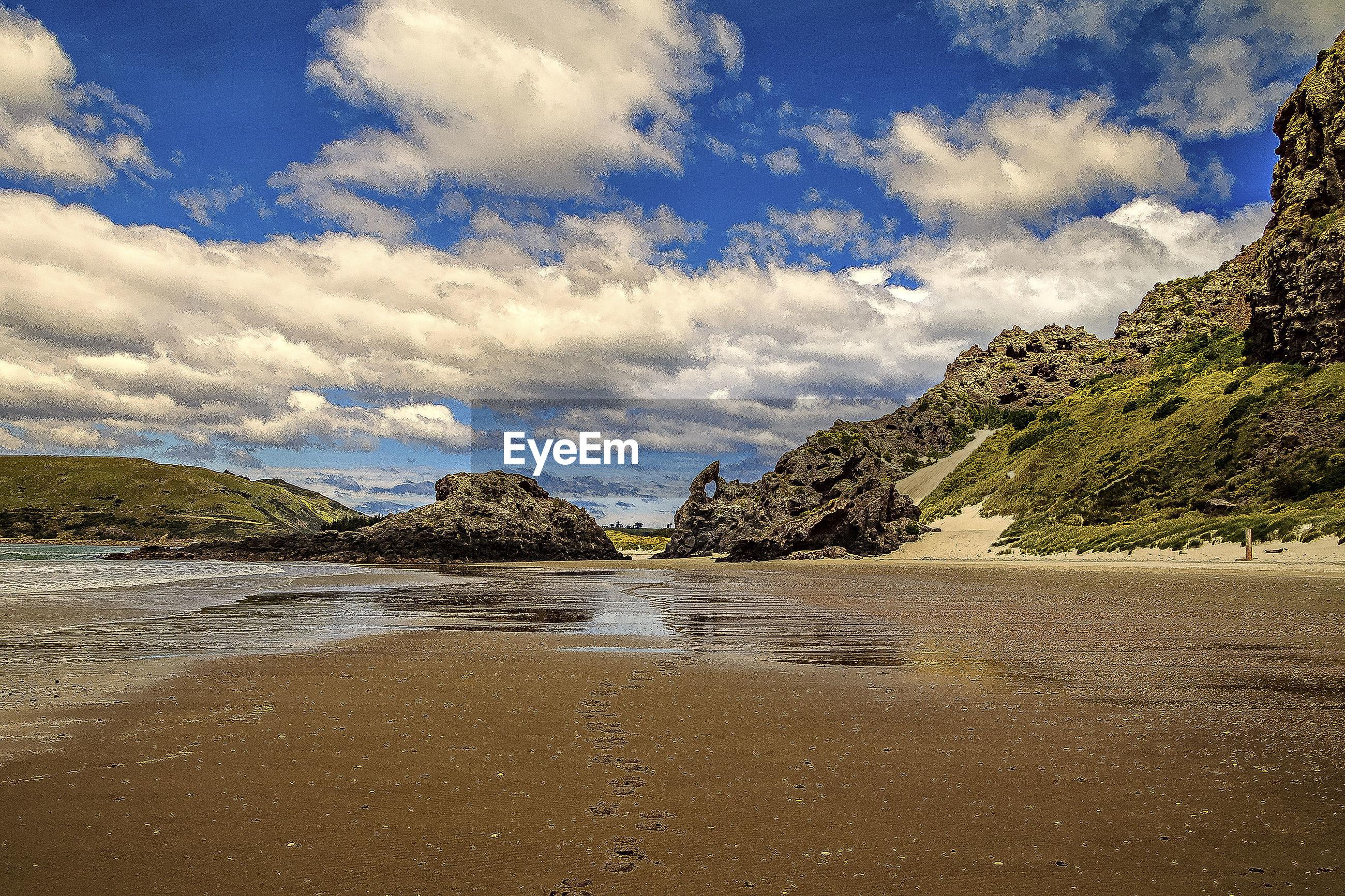 FULL FRAME SHOT OF WET BEACH AGAINST SKY