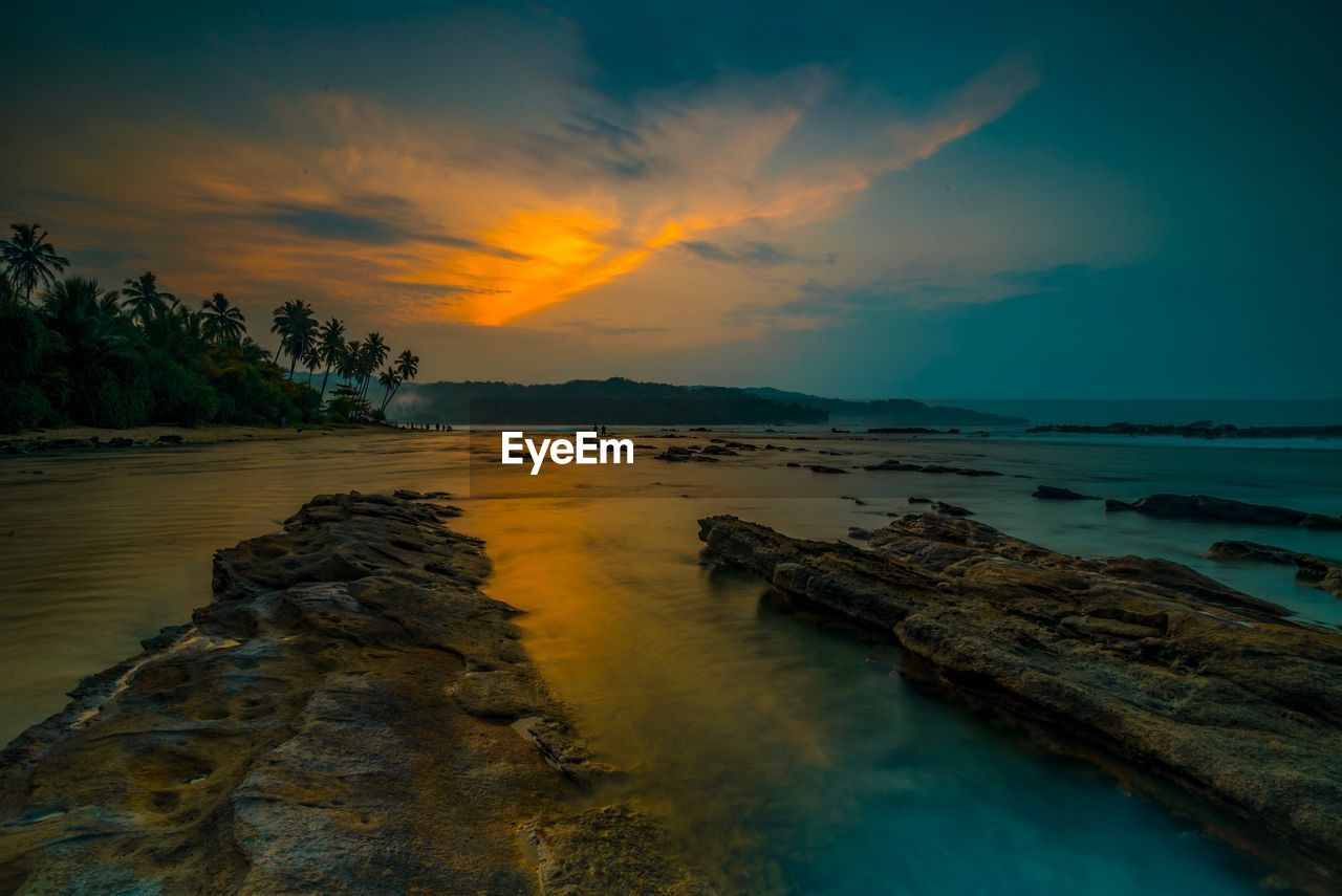 sky, water, sunset, scenics - nature, beauty in nature, tranquil scene, cloud - sky, tranquility, sea, nature, rock, solid, no people, rock - object, non-urban scene, land, idyllic, beach, orange color, outdoors