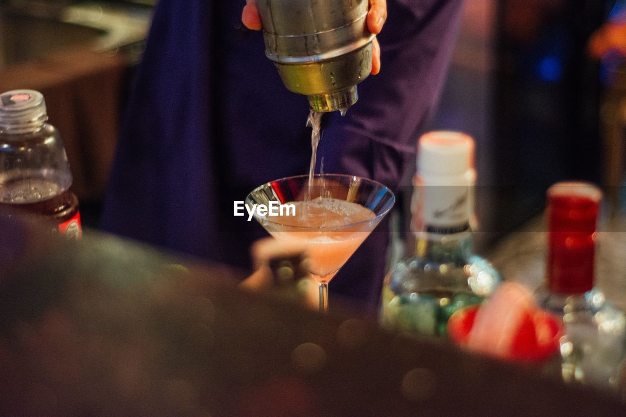 Midsection of person pouring drink in glass at bar
