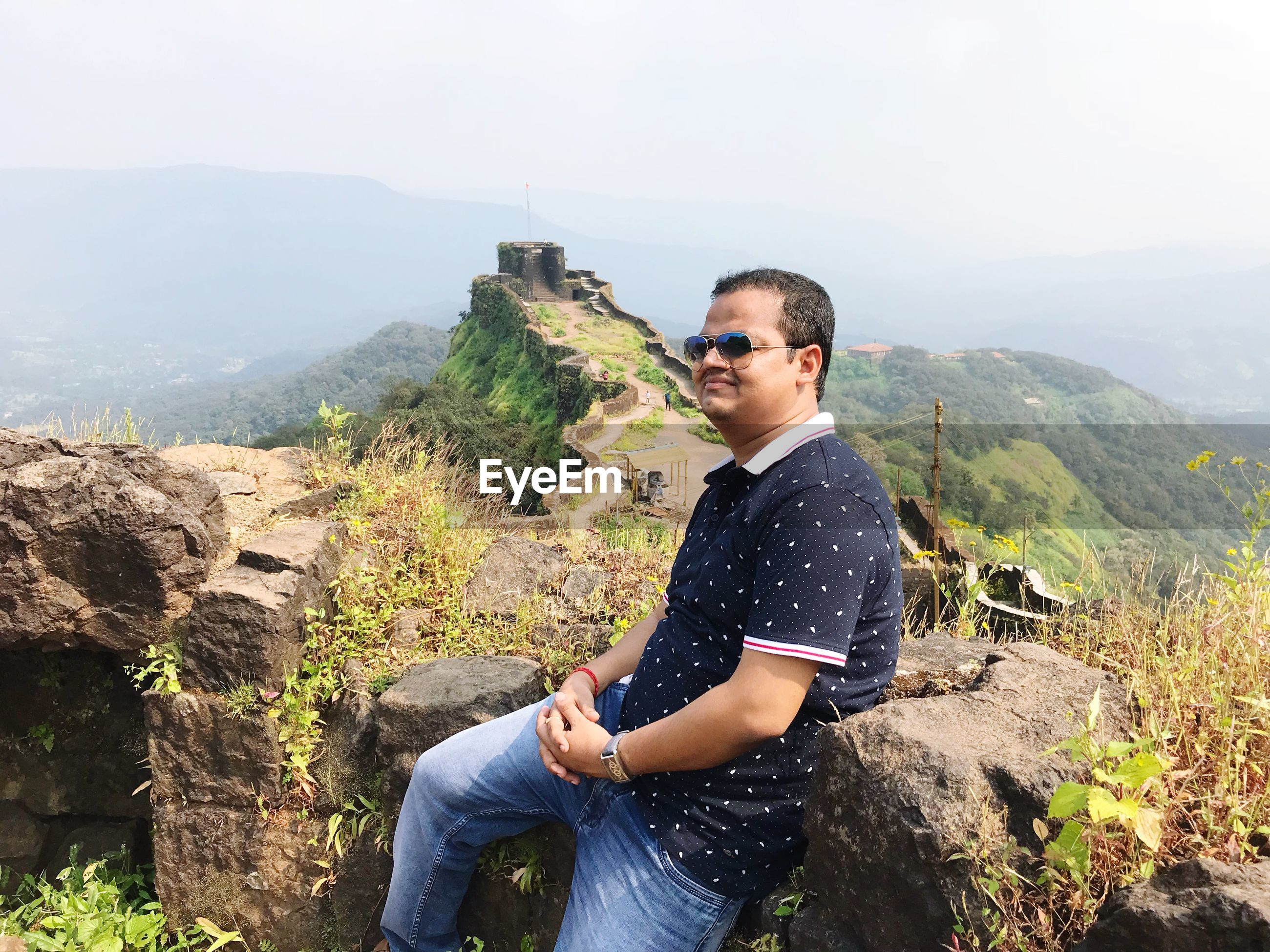 Side view of man sitting on rock against mountain range