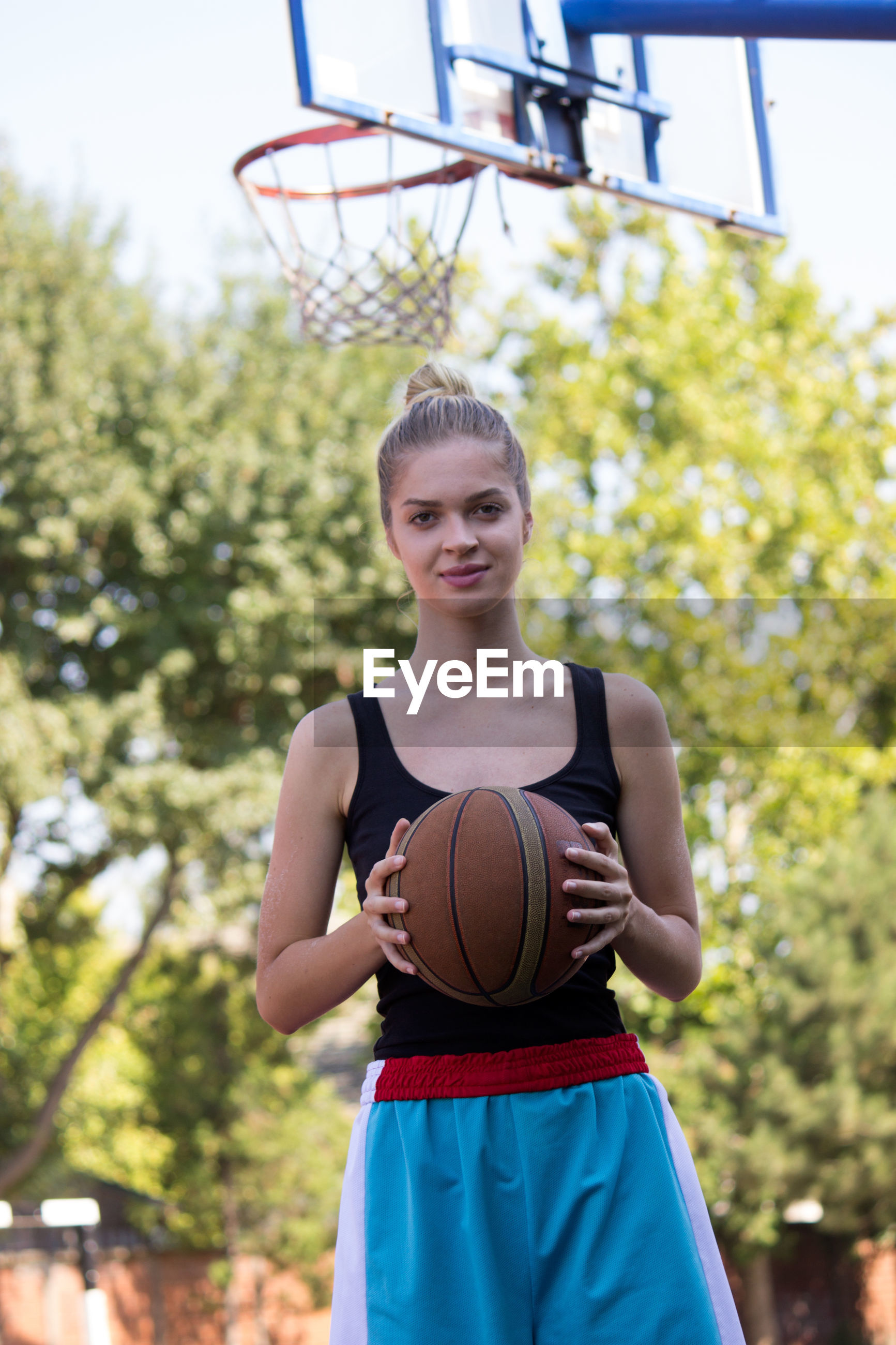 Portrait of young woman holding basketball in court