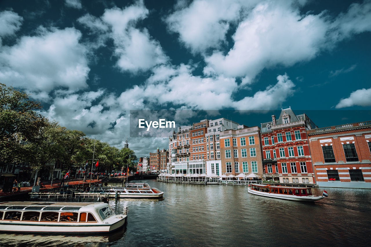 cloud - sky, transportation, building exterior, water, nautical vessel, mode of transportation, architecture, built structure, sky, city, waterfront, nature, tree, day, moored, river, no people, outdoors, plant, passenger craft, cruise ship
