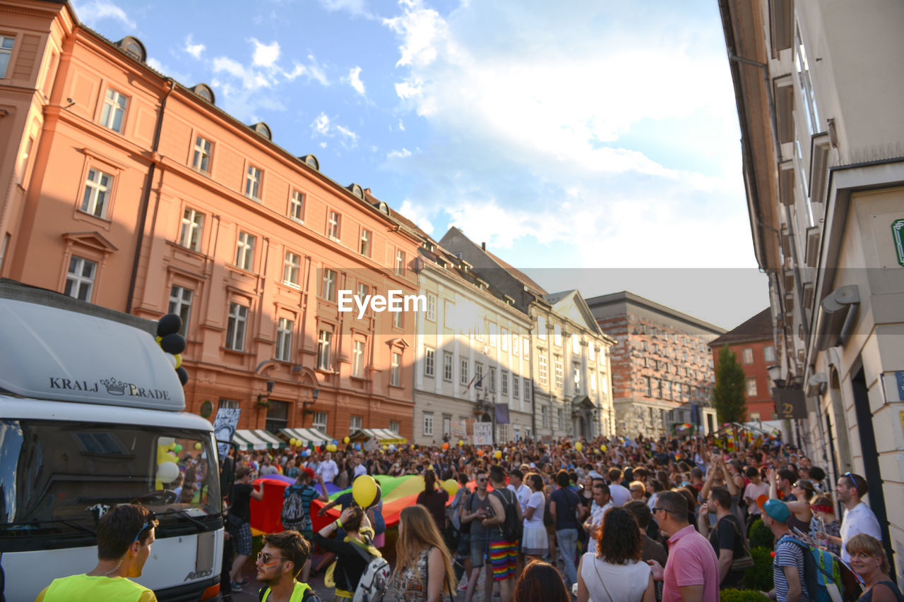 large group of people, building exterior, architecture, sky, built structure, city, street, cloud - sky, real people, men, crowd, outdoors, day, women, people