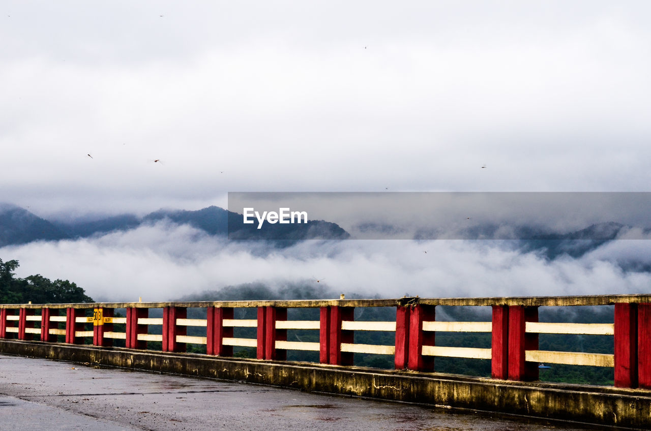 View Of Bridge Against Foggy Mountains
