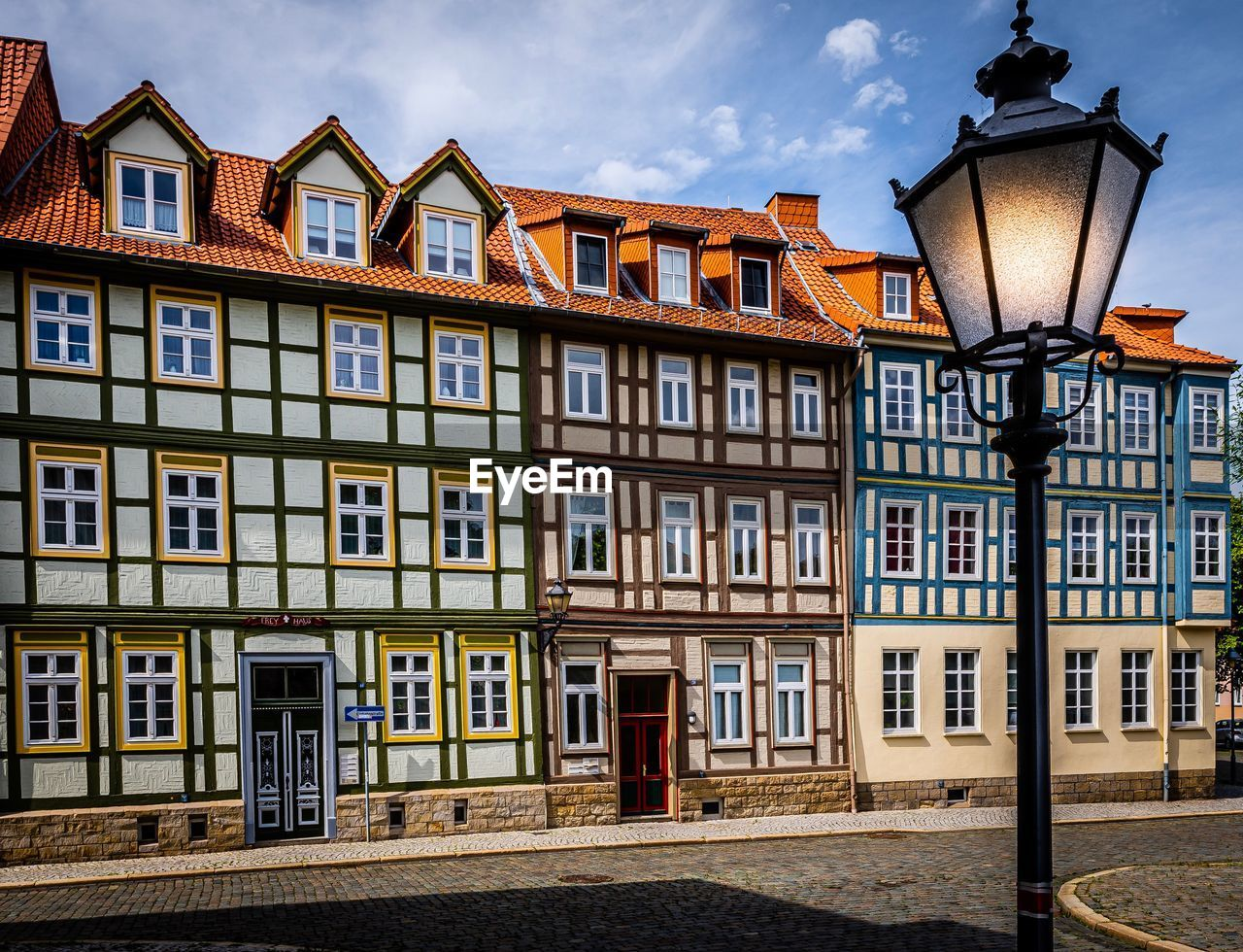 building exterior, architecture, built structure, street, building, lighting equipment, street light, window, city, residential district, no people, house, sky, in a row, cloud - sky, row house, day, outdoors, nature, side by side, electric lamp