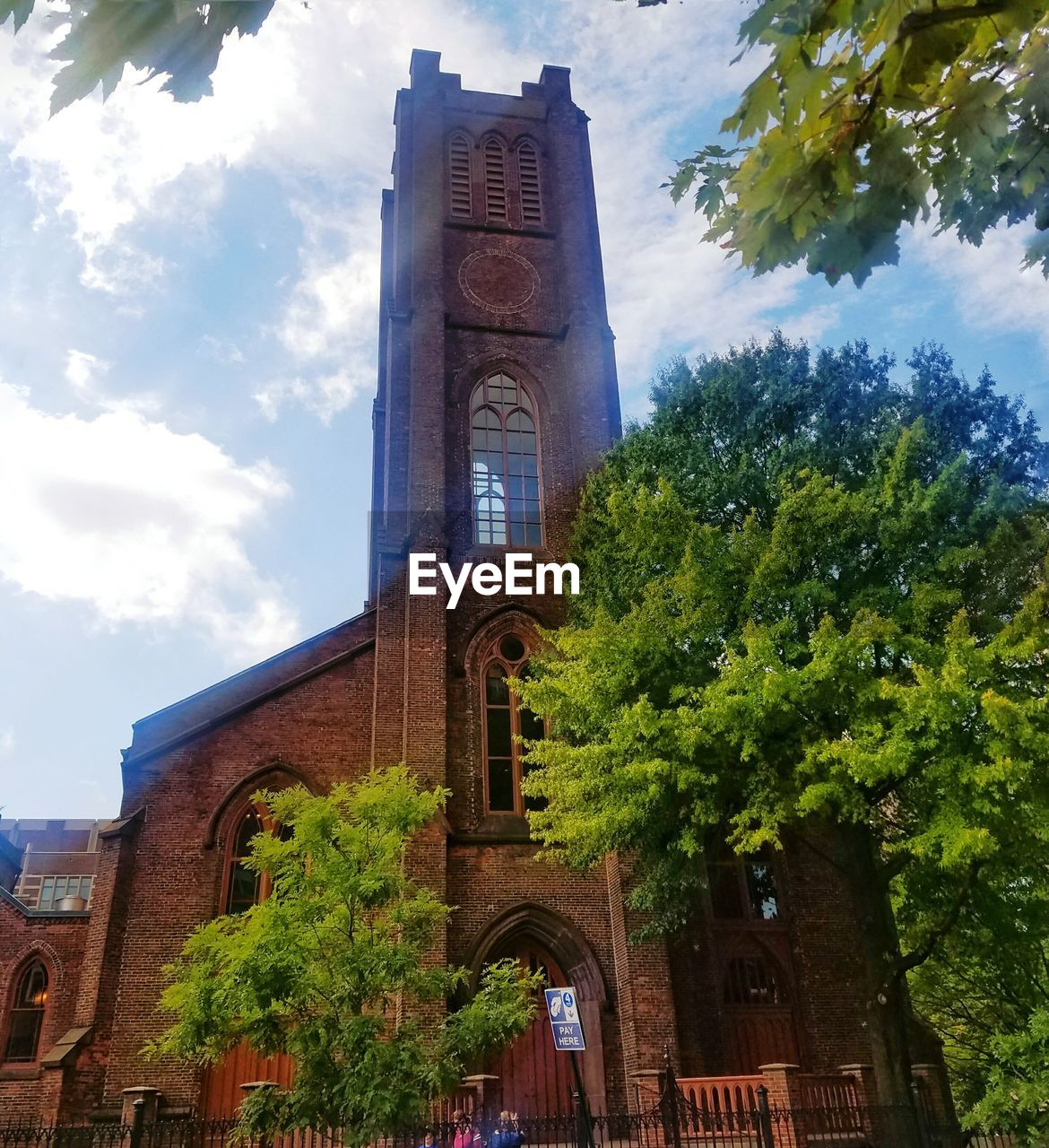 architecture, religion, tree, built structure, low angle view, place of worship, building exterior, spirituality, cloud - sky, sky, day, no people, history, outdoors, bell tower, cross