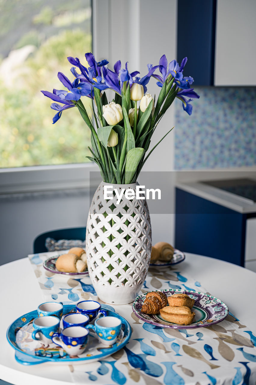 Close-up of breakfast and flower vase on table