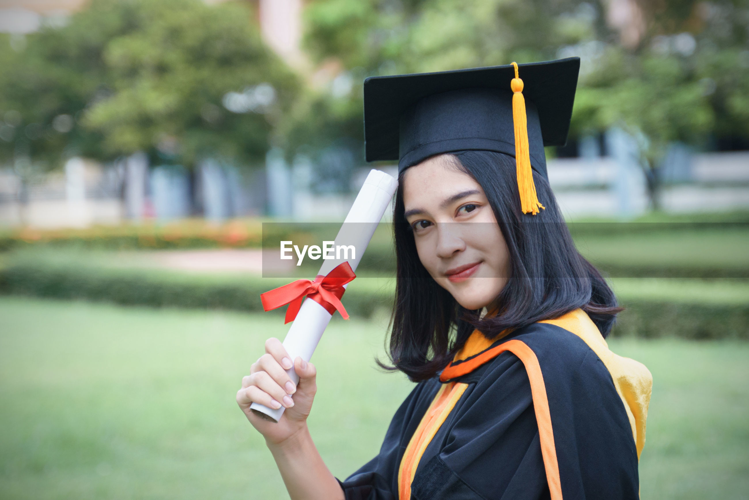 Portrait of smiling young woman in graduation gown standing outdoors