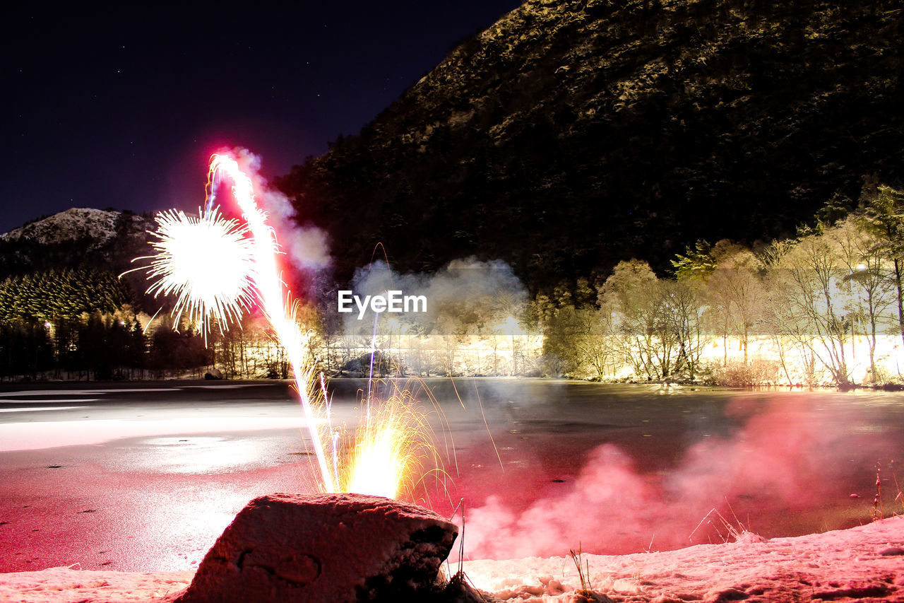long exposure, motion, smoke - physical structure, glowing, night, exploding, blurred motion, burning, firework - man made object, firework display, illuminated, outdoors, no people, sky, water, nature, firework, tree, beauty in nature