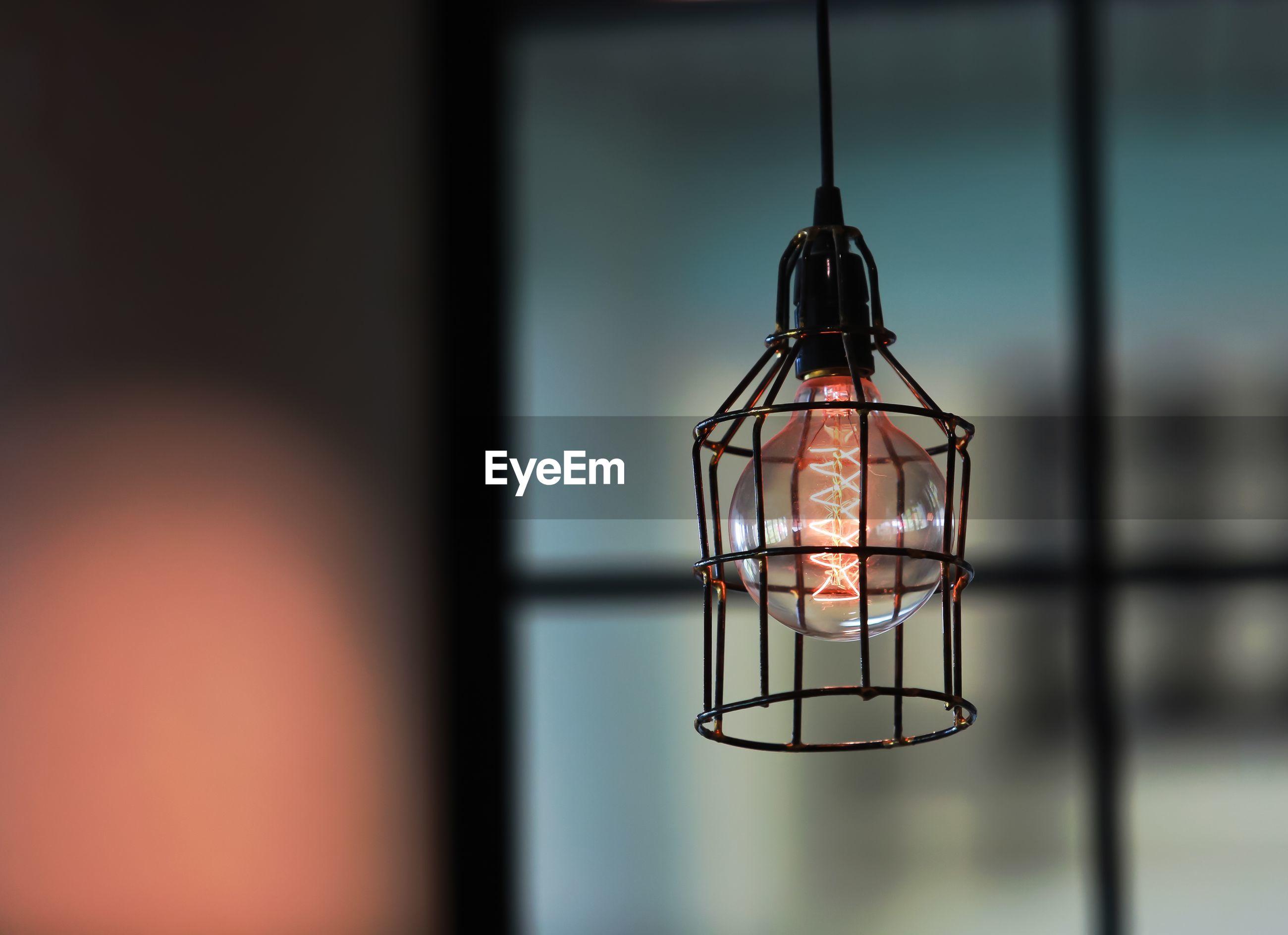 Illuminated light bulb hanging against window