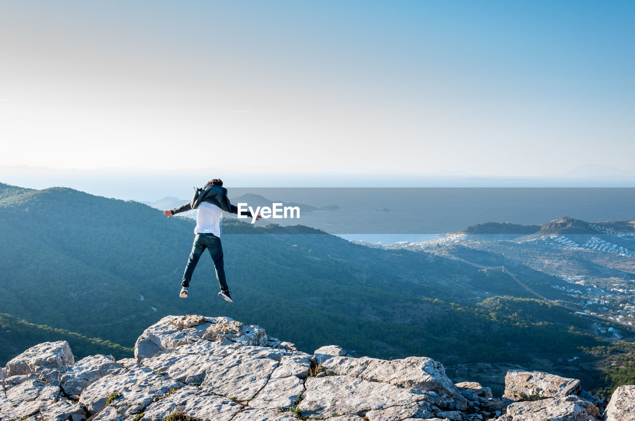Full Length Rear View Of Man Jumping On Rock At Mountain Peak