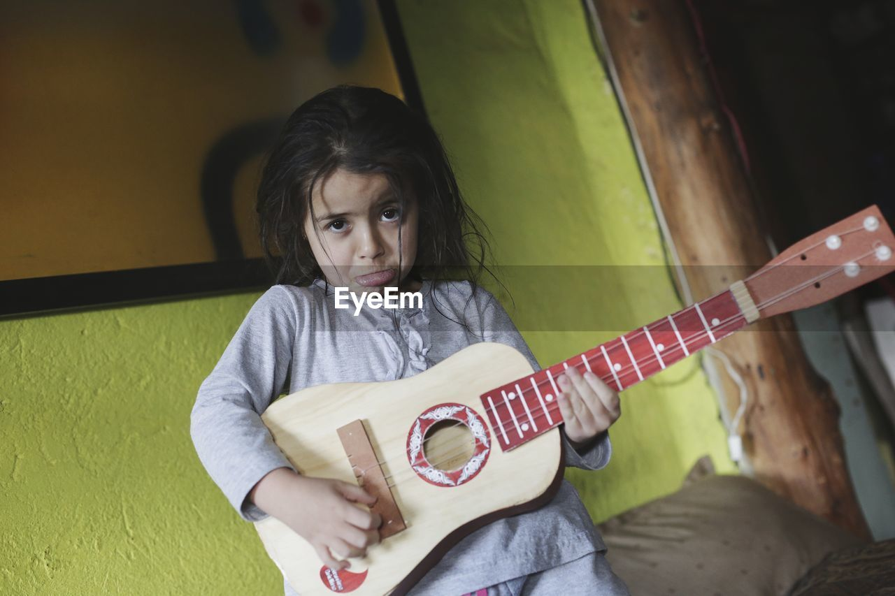 Portrait Of Girl Making Face While Playing Guitar At Home