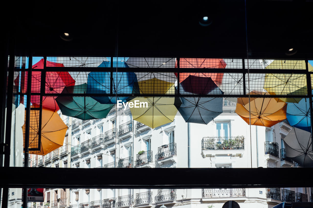 Low angle view of colorful umbrellas seen through window in city