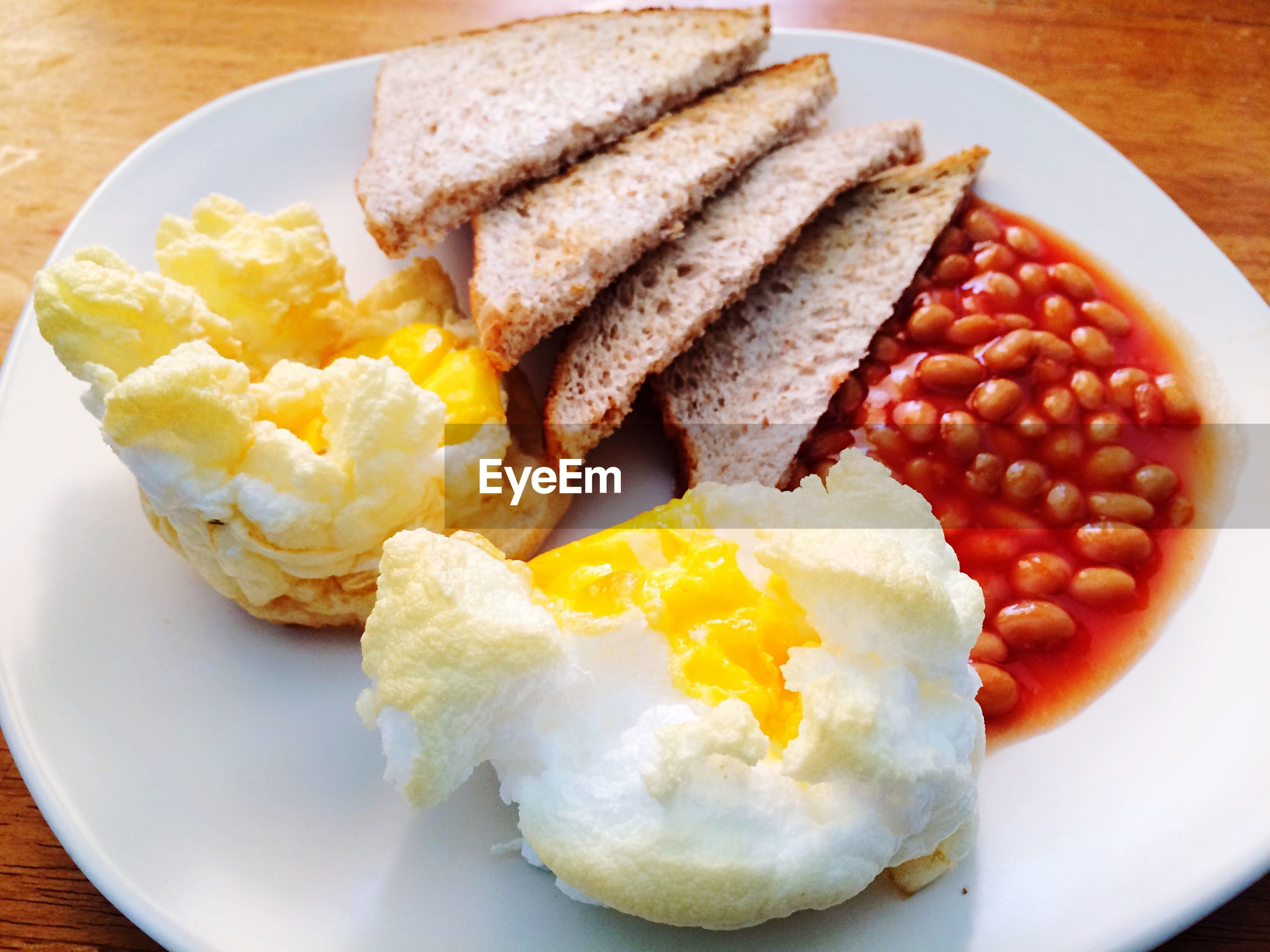 Mashed eggs with bread on plate