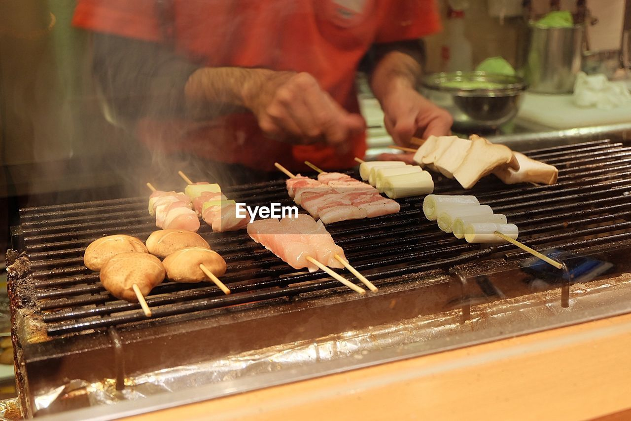 food and drink, food, freshness, barbecue, meat, real people, preparation, midsection, heat - temperature, barbecue grill, grilled, one person, preparing food, skewer, human hand, kitchen, holding, hand, business, japanese food, beef, street food, temptation