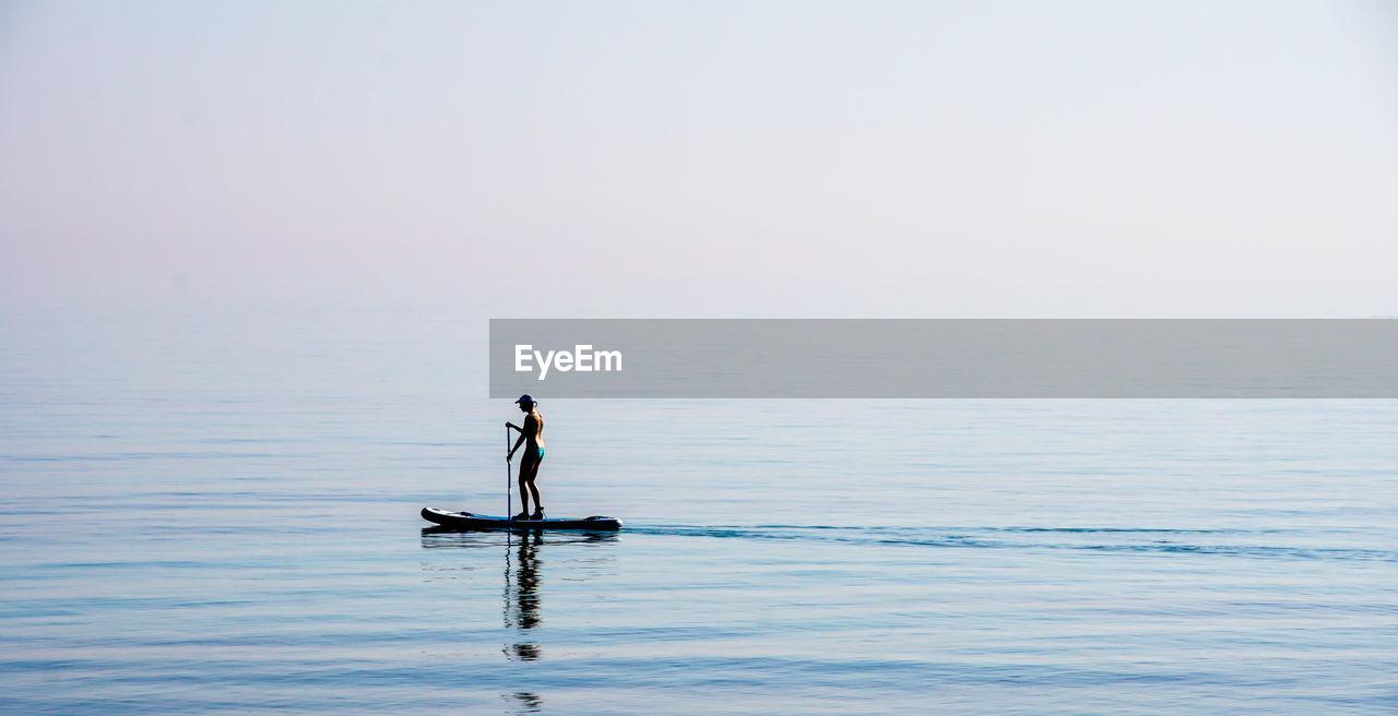 Man Paddleboarding In Sea Against Sky