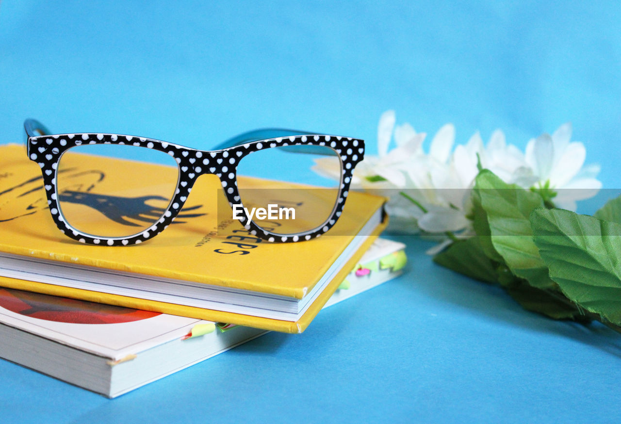Close-up of eyeglasses on book by artificial flowers over blue background