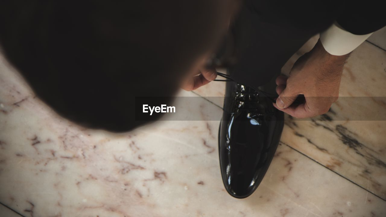 Low section of businessman tying shoelace on marble floor
