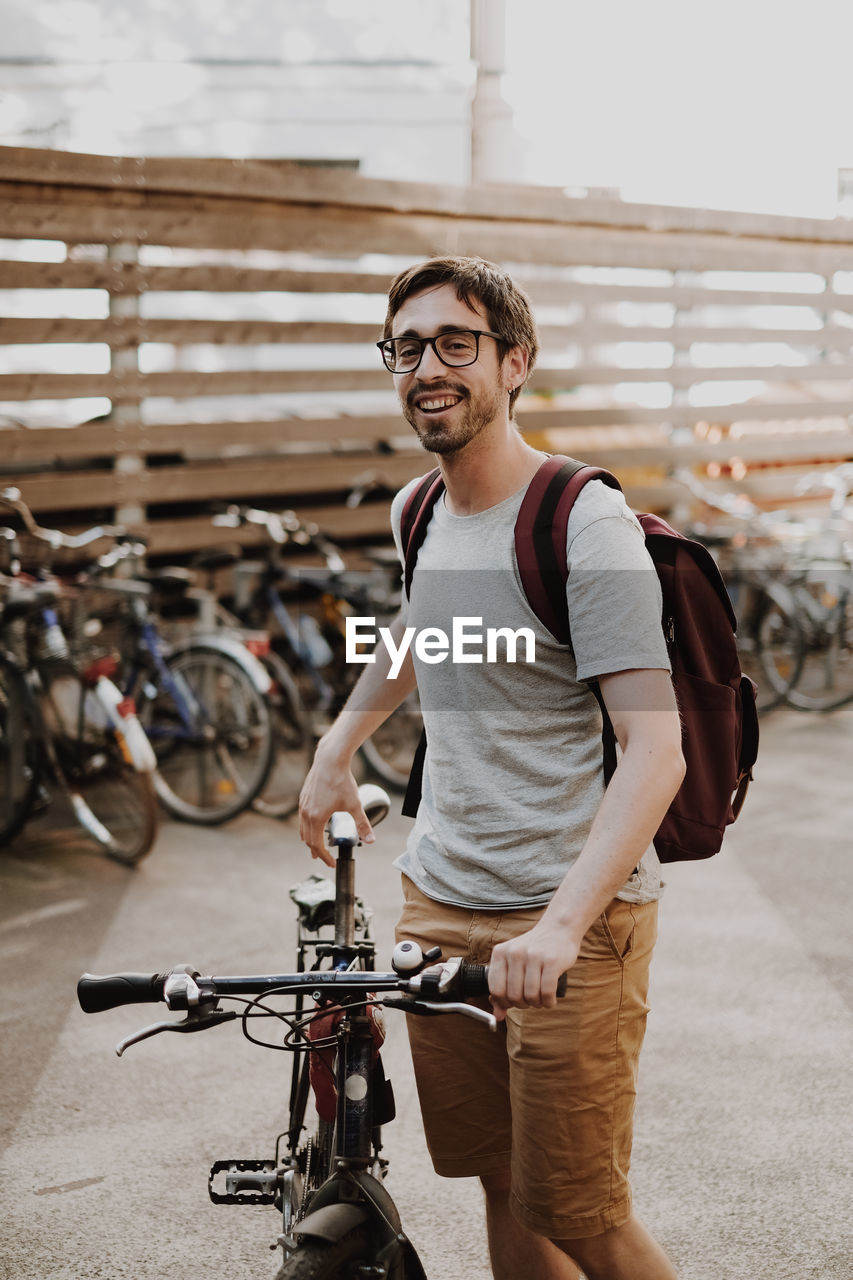 Portrait of smiling young man with bicycle in city