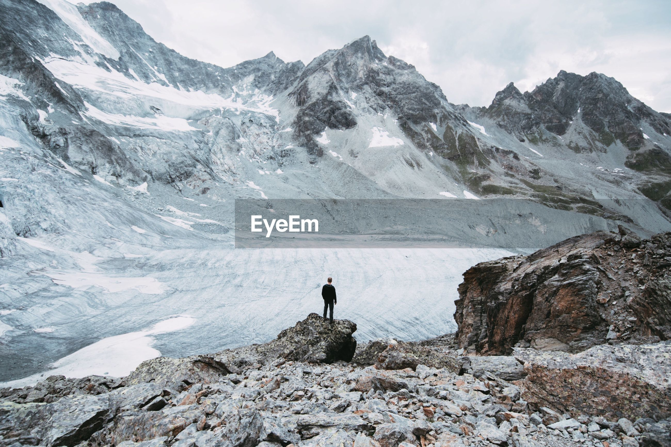 High angle view of man standing on rock formation in front of swiss alps
