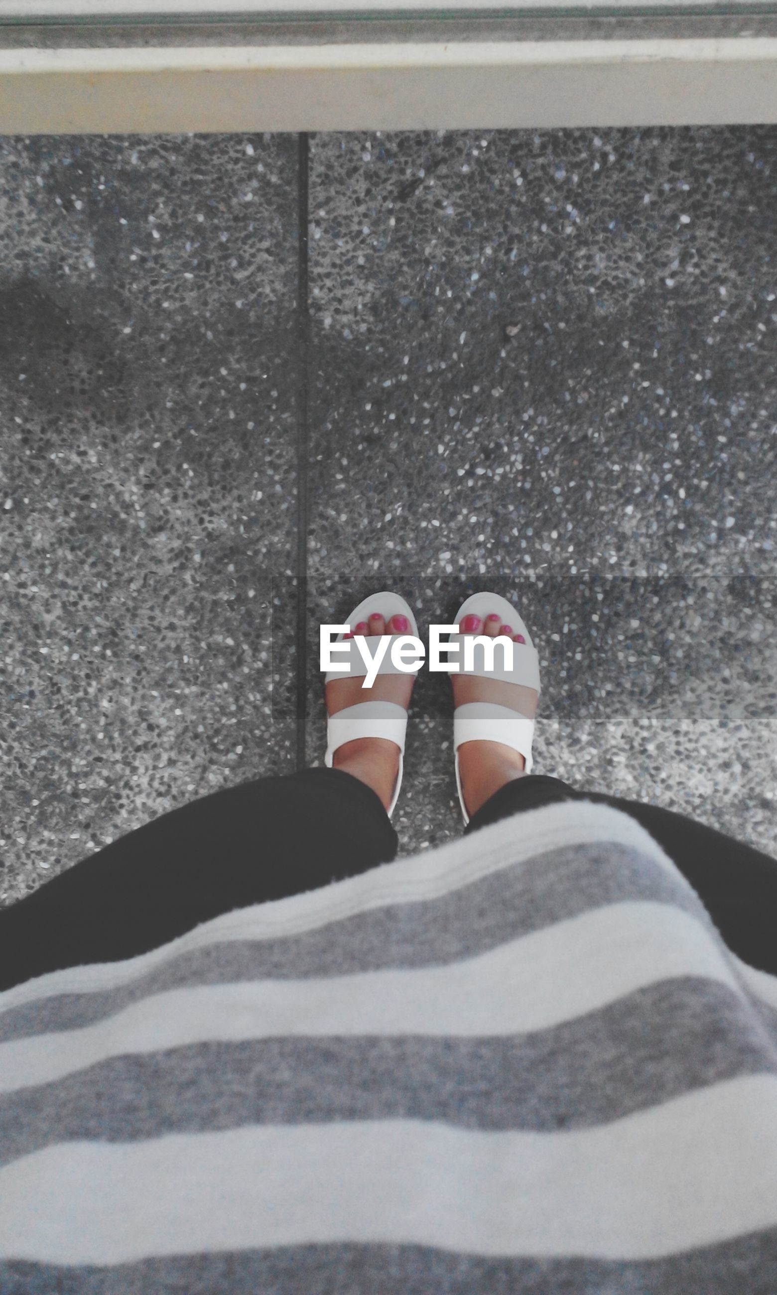 low section, person, shoe, personal perspective, footwear, high angle view, human foot, lifestyles, standing, leisure activity, street, jeans, close-up, day, canvas shoe, casual clothing