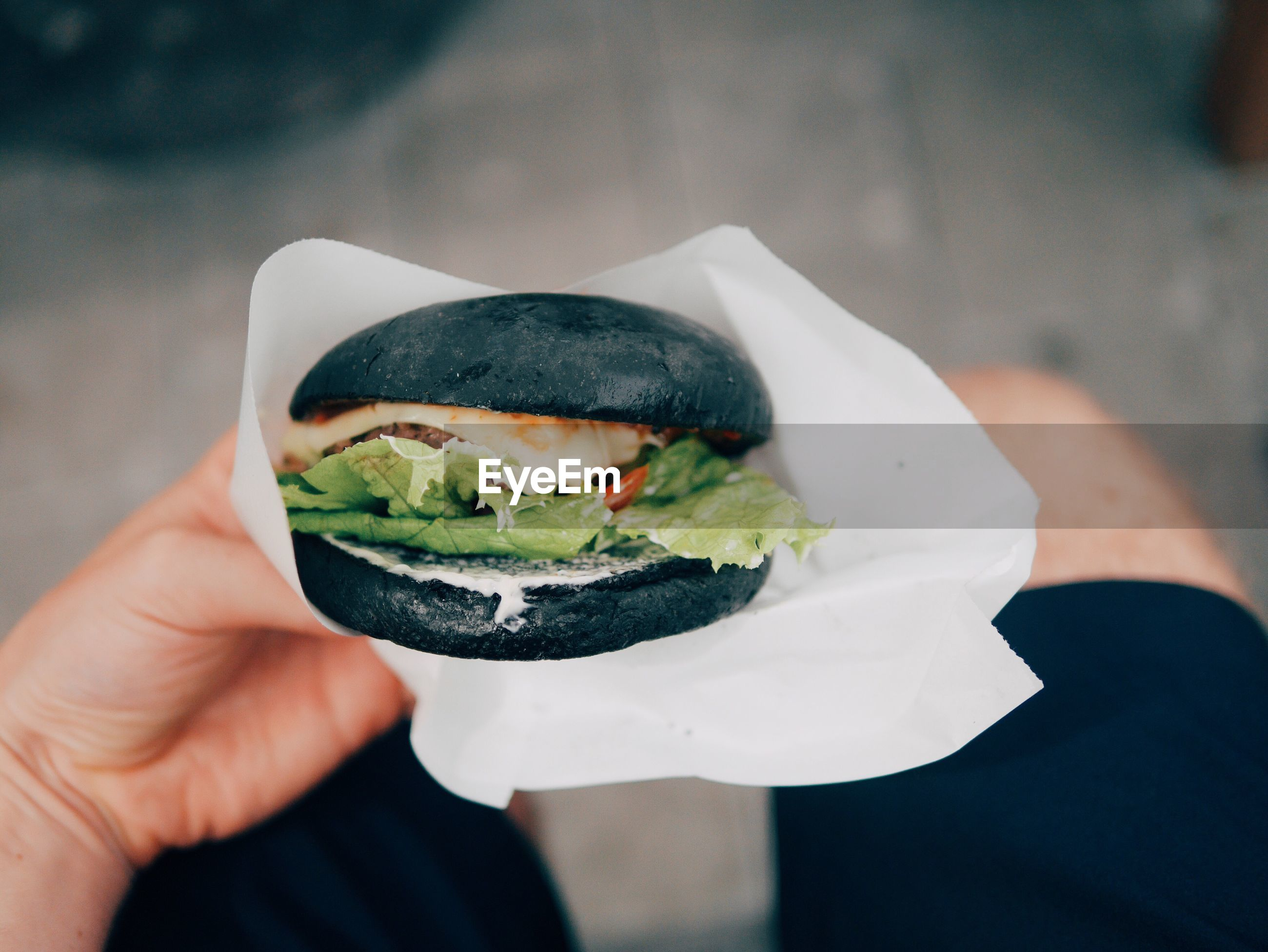 Midsection of man holding black burger
