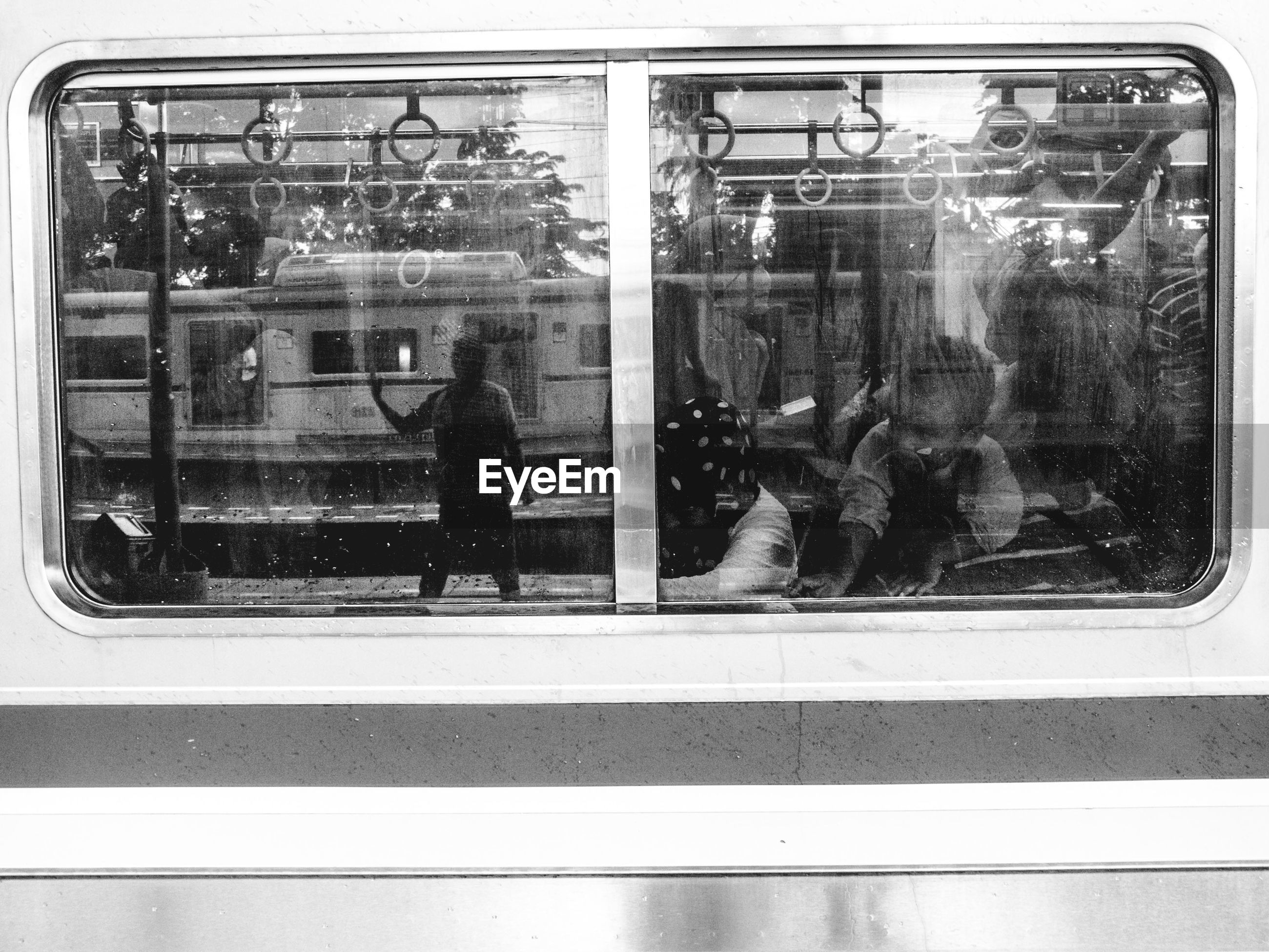 People traveling in train with man at railroad station reflecting on window