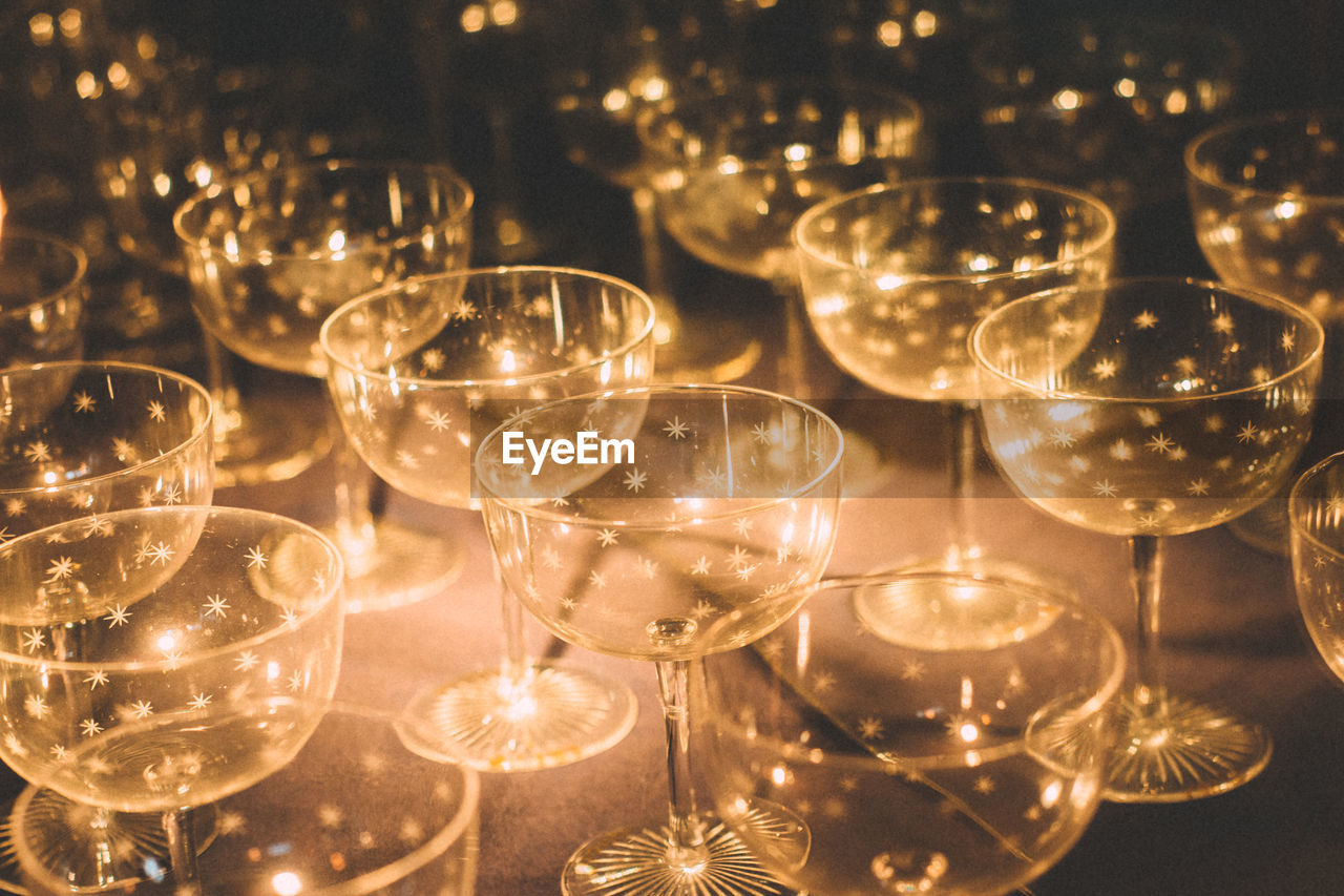 glass, illuminated, wineglass, glass - material, alcohol, refreshment, indoors, no people, drink, wine, table, transparent, close-up, household equipment, drinking glass, food and drink, still life, celebration, glowing, large group of objects
