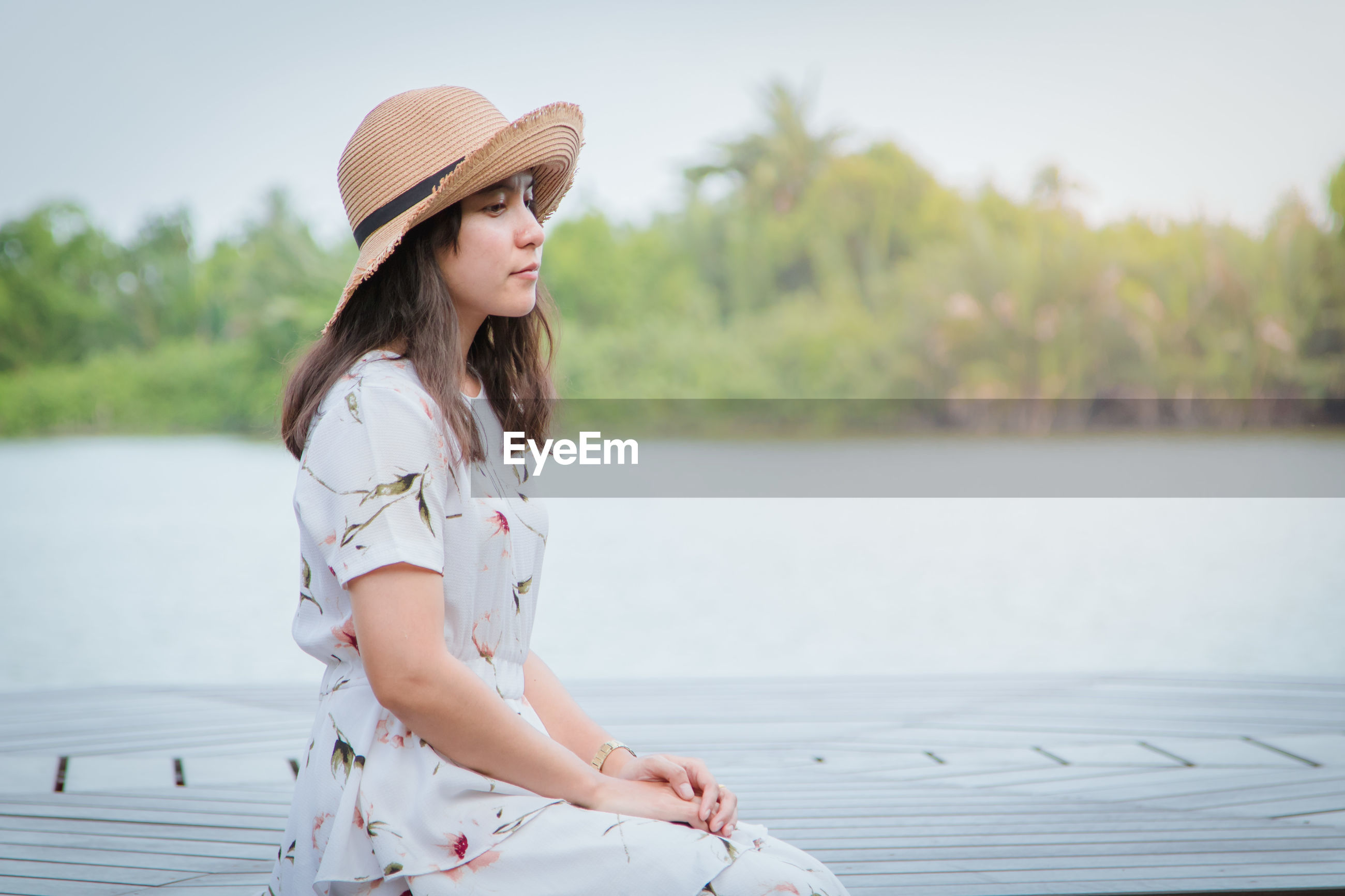 Side view of thoughtful young woman wearing hat while sitting on pier over lake