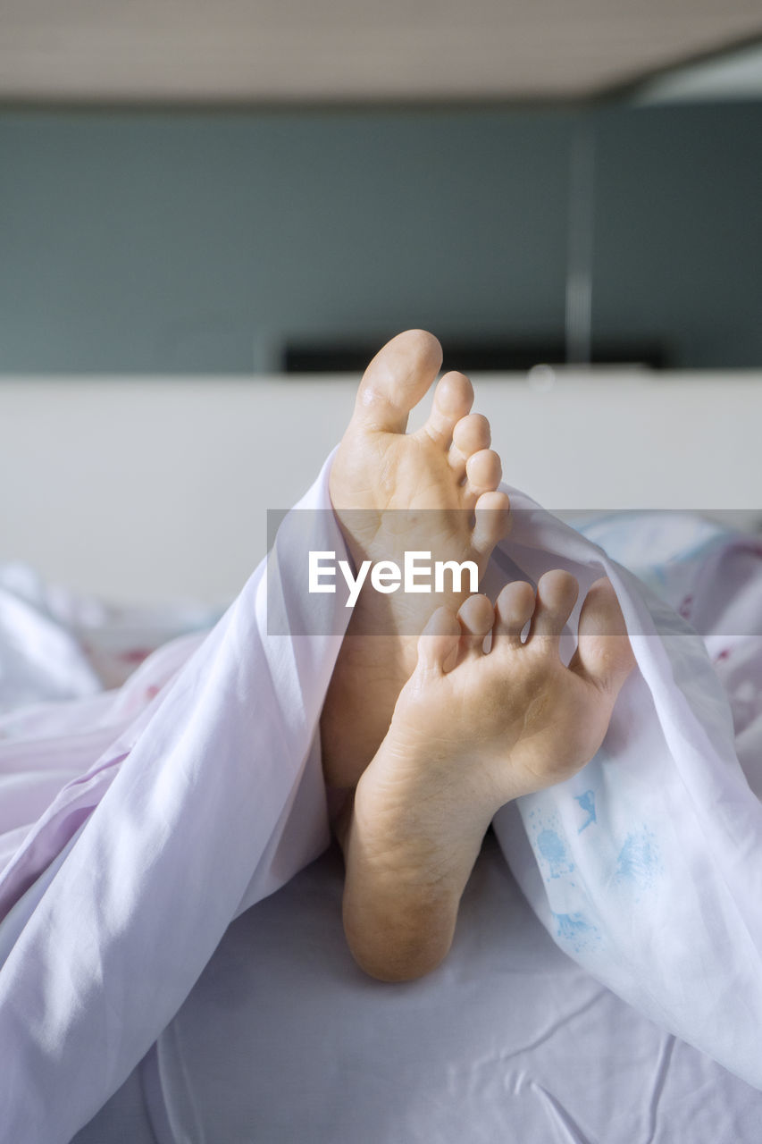 barefoot, human body part, bed, human foot, indoors, real people, lying down, body part, furniture, close-up, relaxation, human hand, hospital, people, healthcare and medicine, human leg, low section, focus on foreground, hand