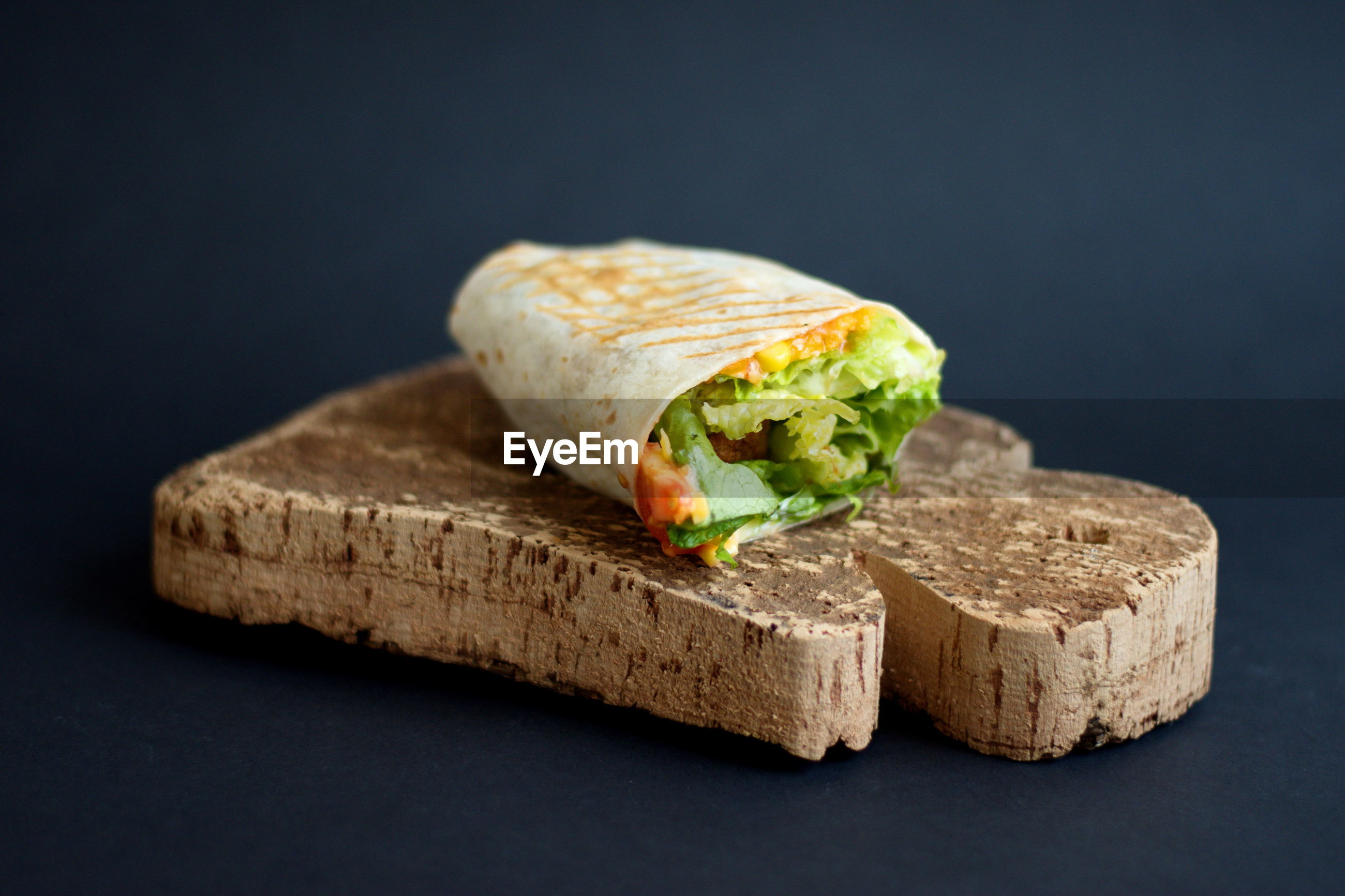 Tortilla with fried chicken meat and vegetables on cutting board against black background
