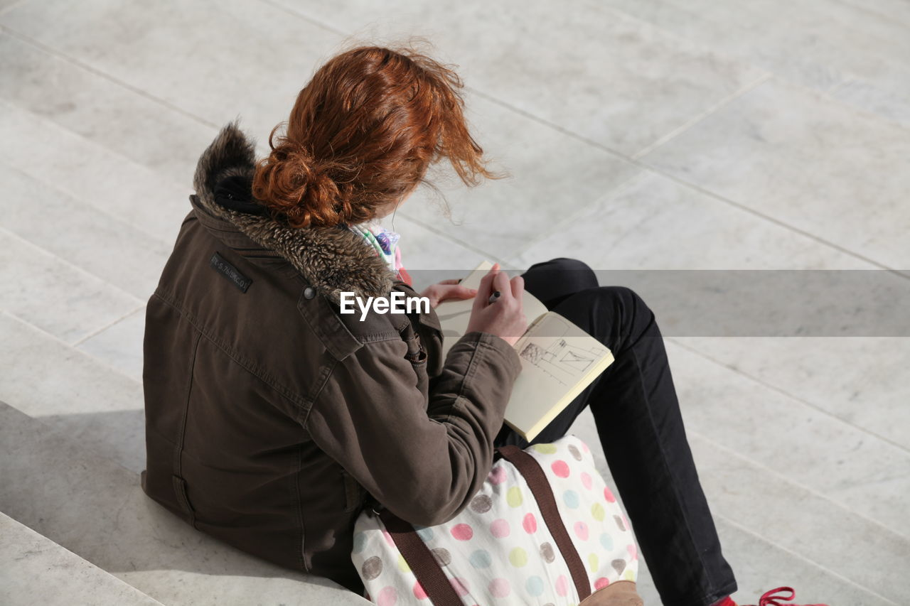 High angle view of woman sitting on steps while holding book