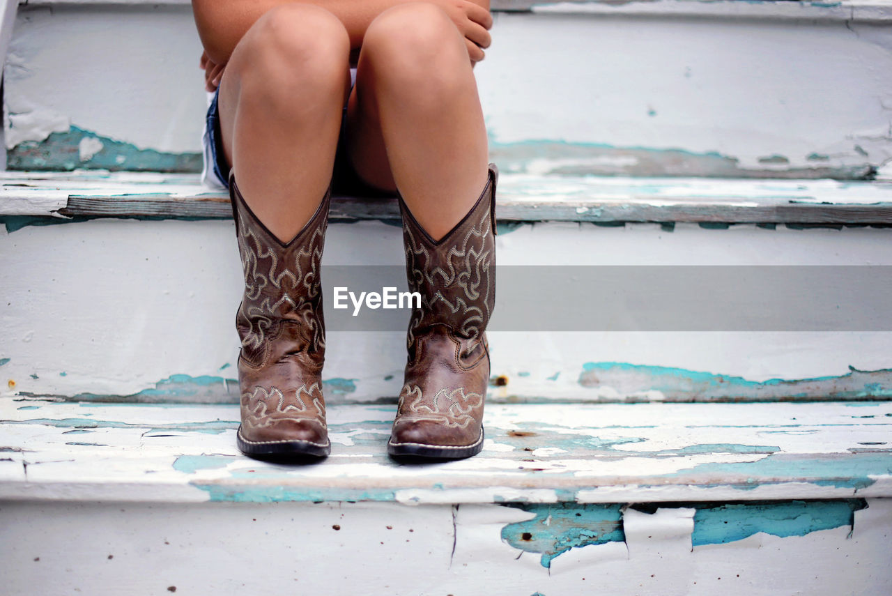 Low Section Of Girl Wearing Cowboy Boot While Sitting On Wooden Steps