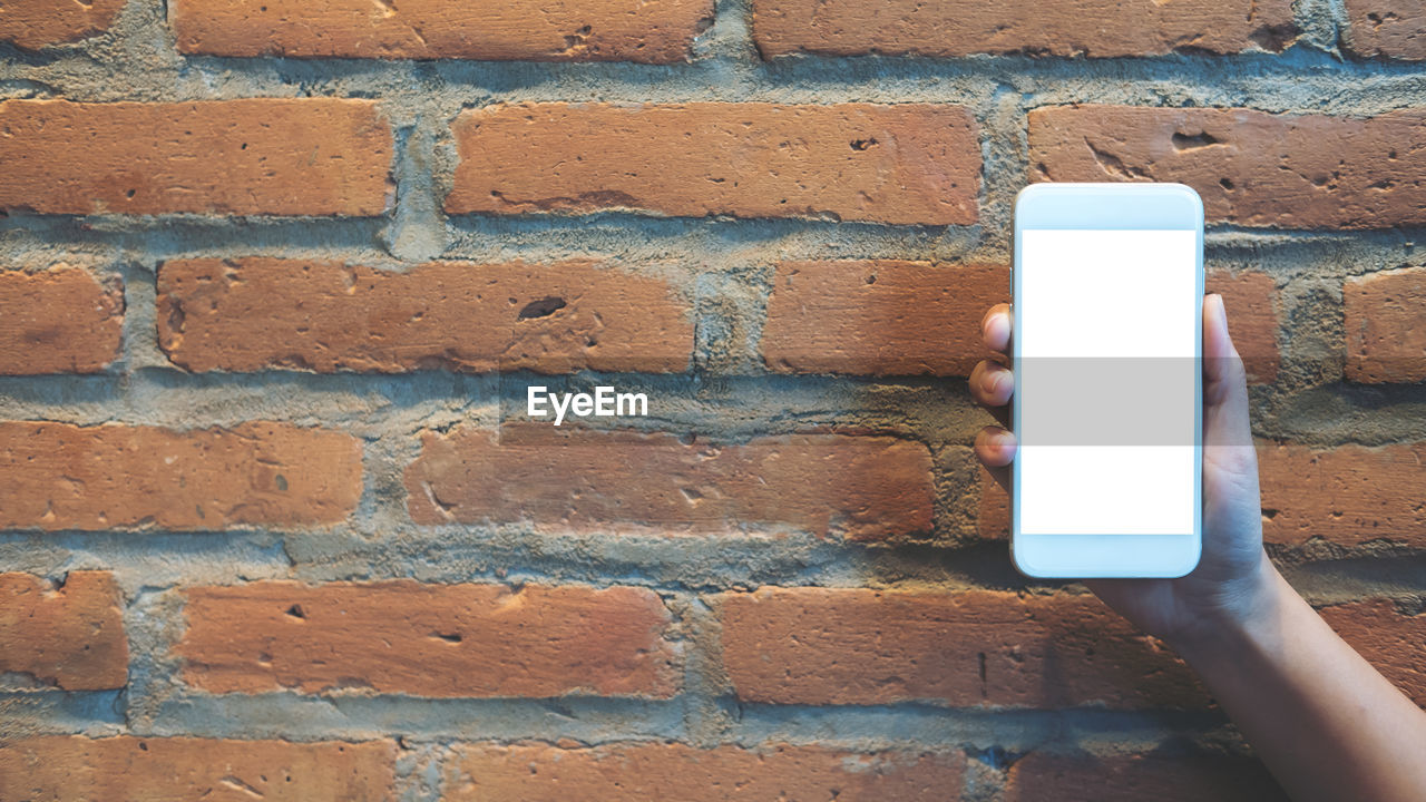 brick wall, wall - building feature, human hand, holding, wall, brick, human body part, hand, one person, built structure, connection, day, white color, architecture, technology, real people, outdoors, close-up, finger