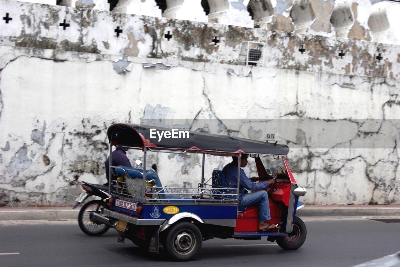 Man riding pedicab on street against wall