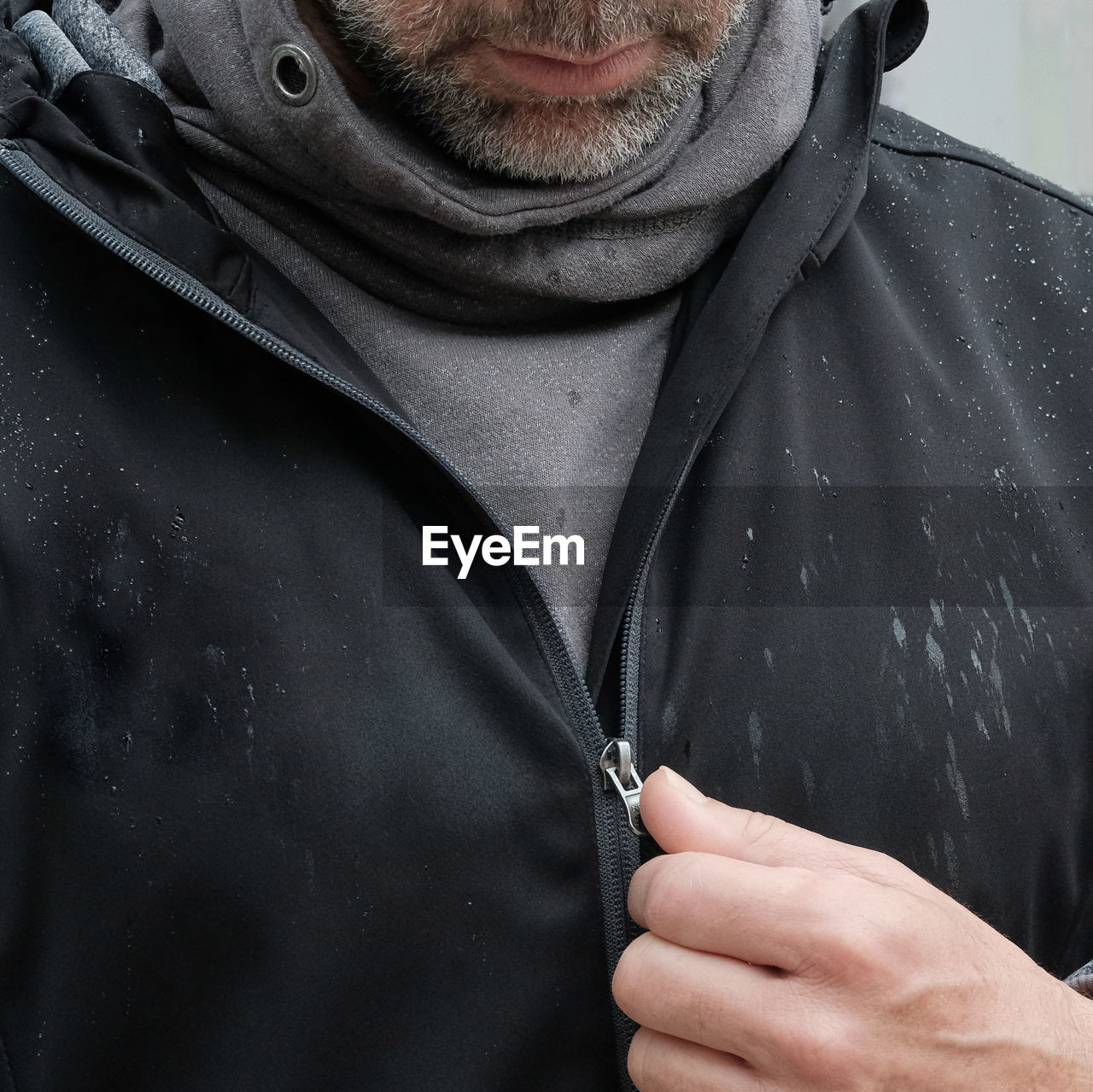 Midsection Of Man Zipping Wet Jacket During Rainy Season