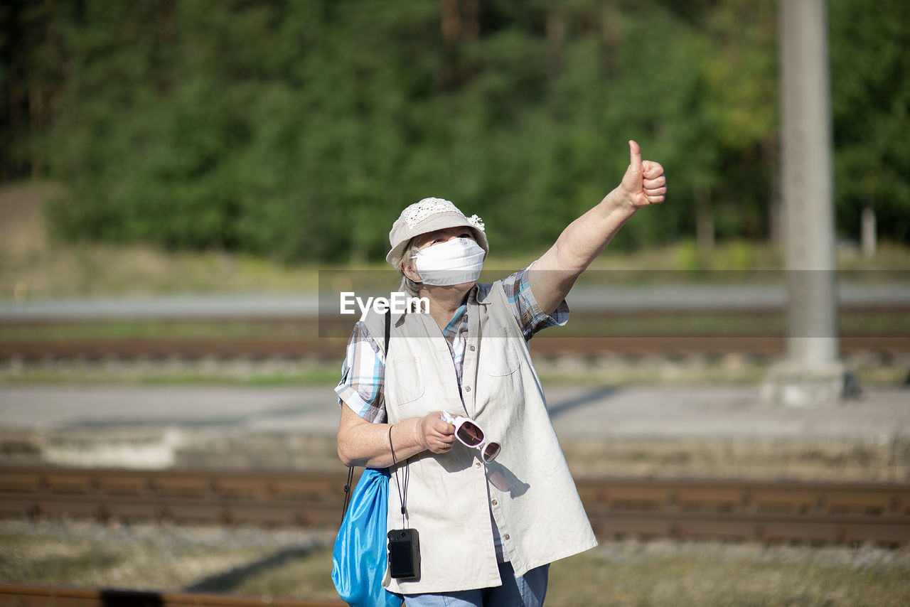 Positive old senior elderly woman with medical face mask,hat and photo camera