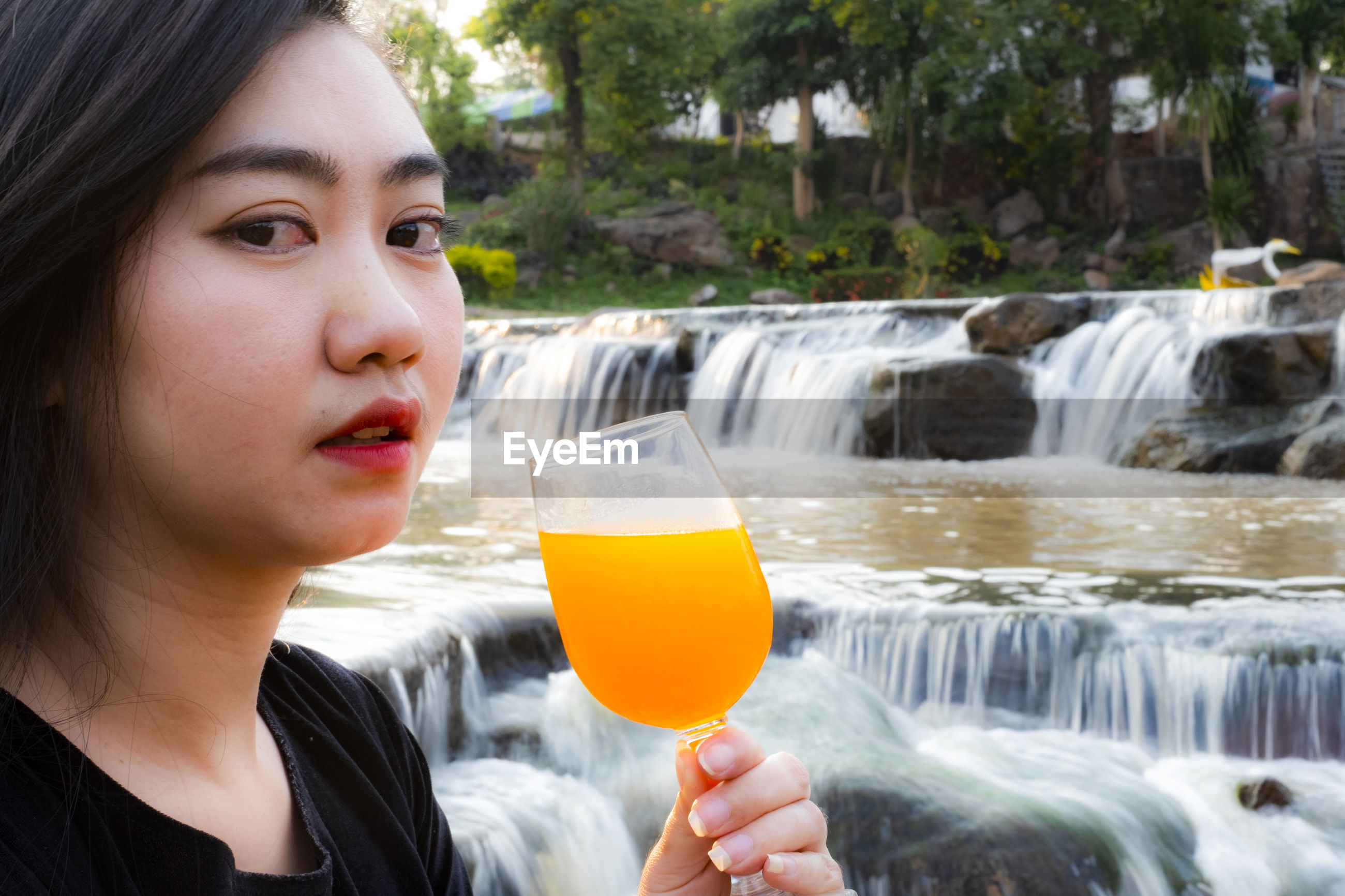 Portrait of woman with juice against waterfall