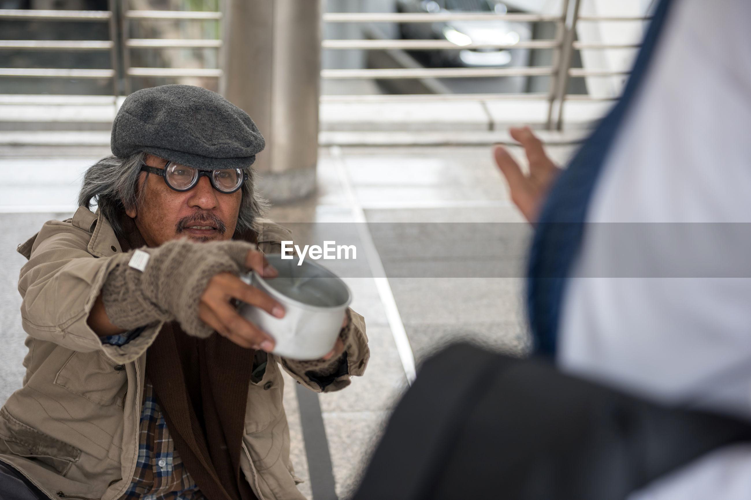 Beggar begging in footbridge